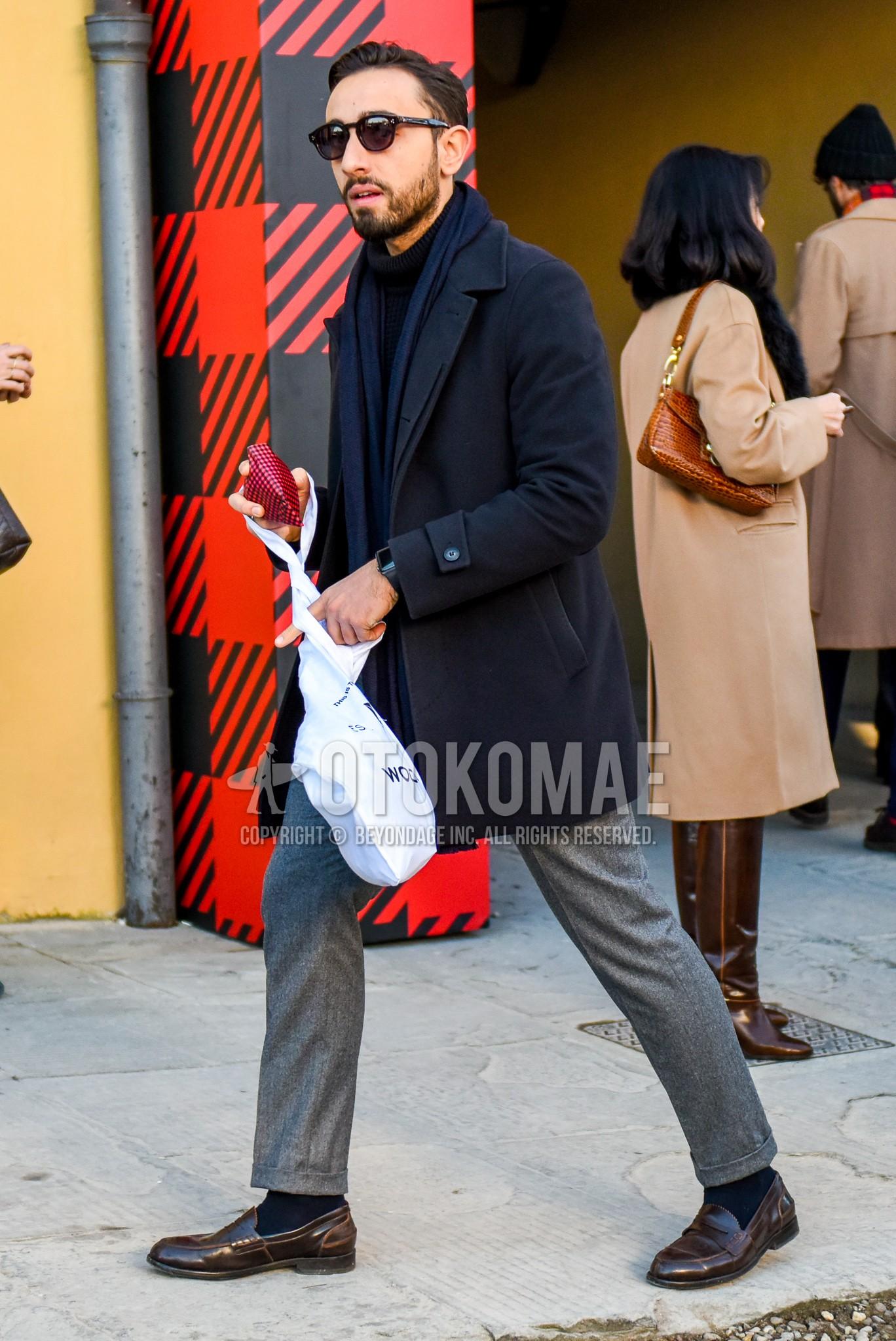 ボストンの黒無地のサングラス、ネイビー無地のマフラー/ストール、ネイビー無地のステンカラーコート、黒無地のタートルネックニット、グレー無地のスラックス、ネイビー無地のソックス、ブラウンコインローファーの革靴を合わせた秋冬のメンズコーデ・着こなし。