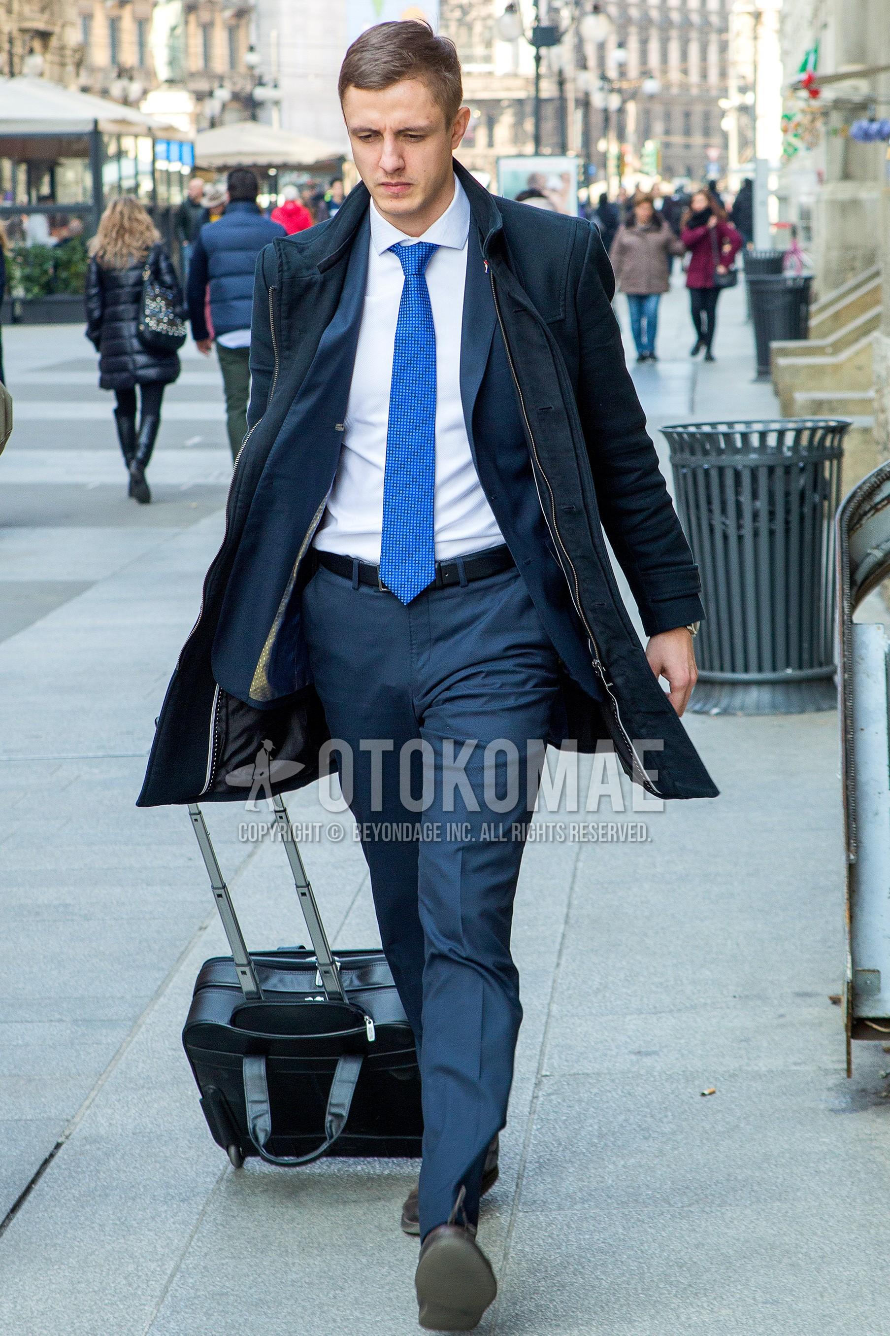 ネイビー無地のステンカラーコート、白無地のシャツ、黒無地のレザーベルト、黒無地のスーツケース、グレー無地のスーツ、ブルーチェックのネクタイを合わせた秋冬のメンズコーデ・着こなし。