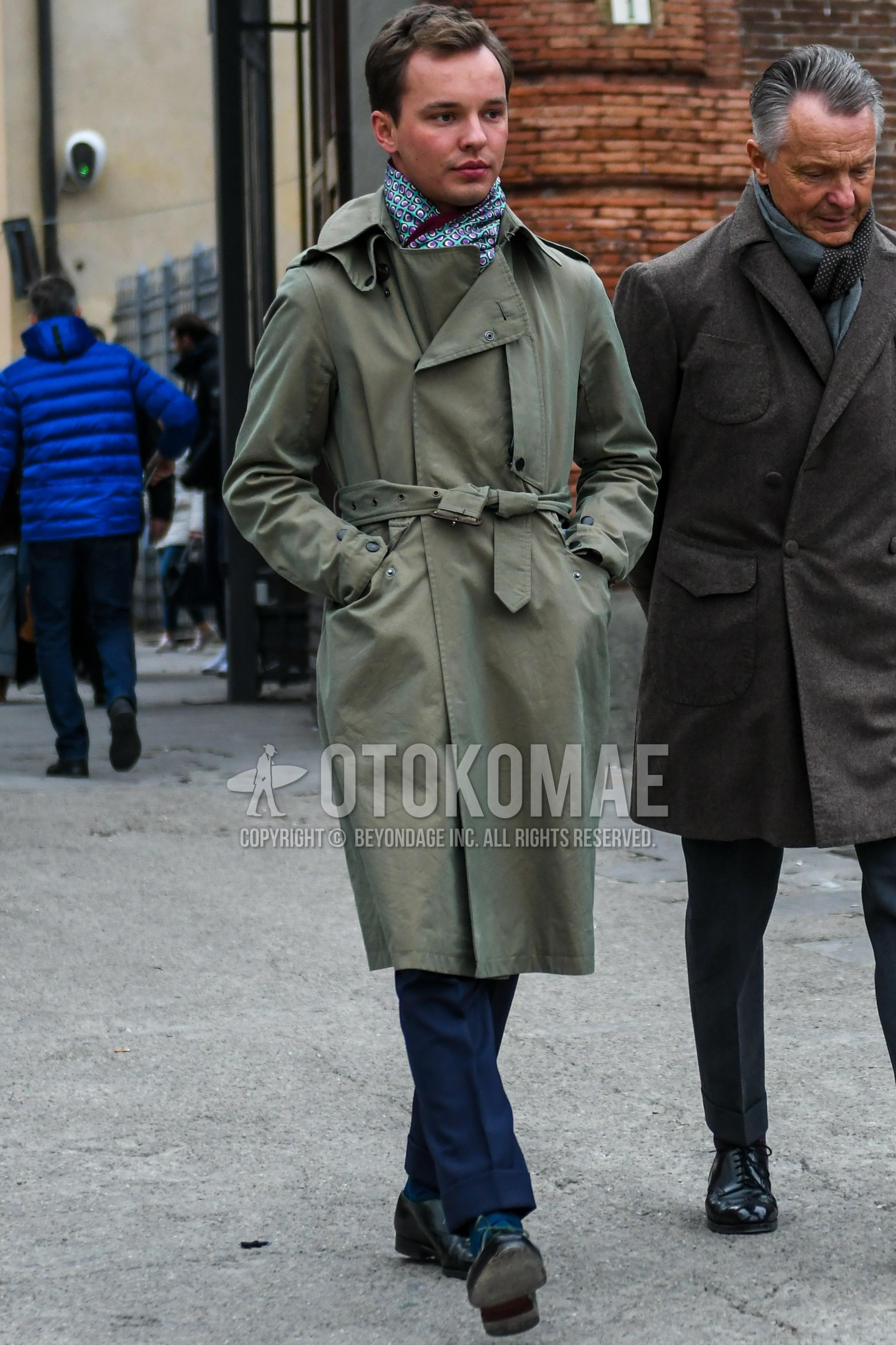 マルチカラー小紋のマフラー/ストール、オリーブグリーン無地のトレンチコート、オリーブグリーン無地のベルテッドコート、グレー無地のスラックス、グレー無地のソックス、黒プレーントゥの革靴を合わせた秋冬のメンズコーデ・着こなし。