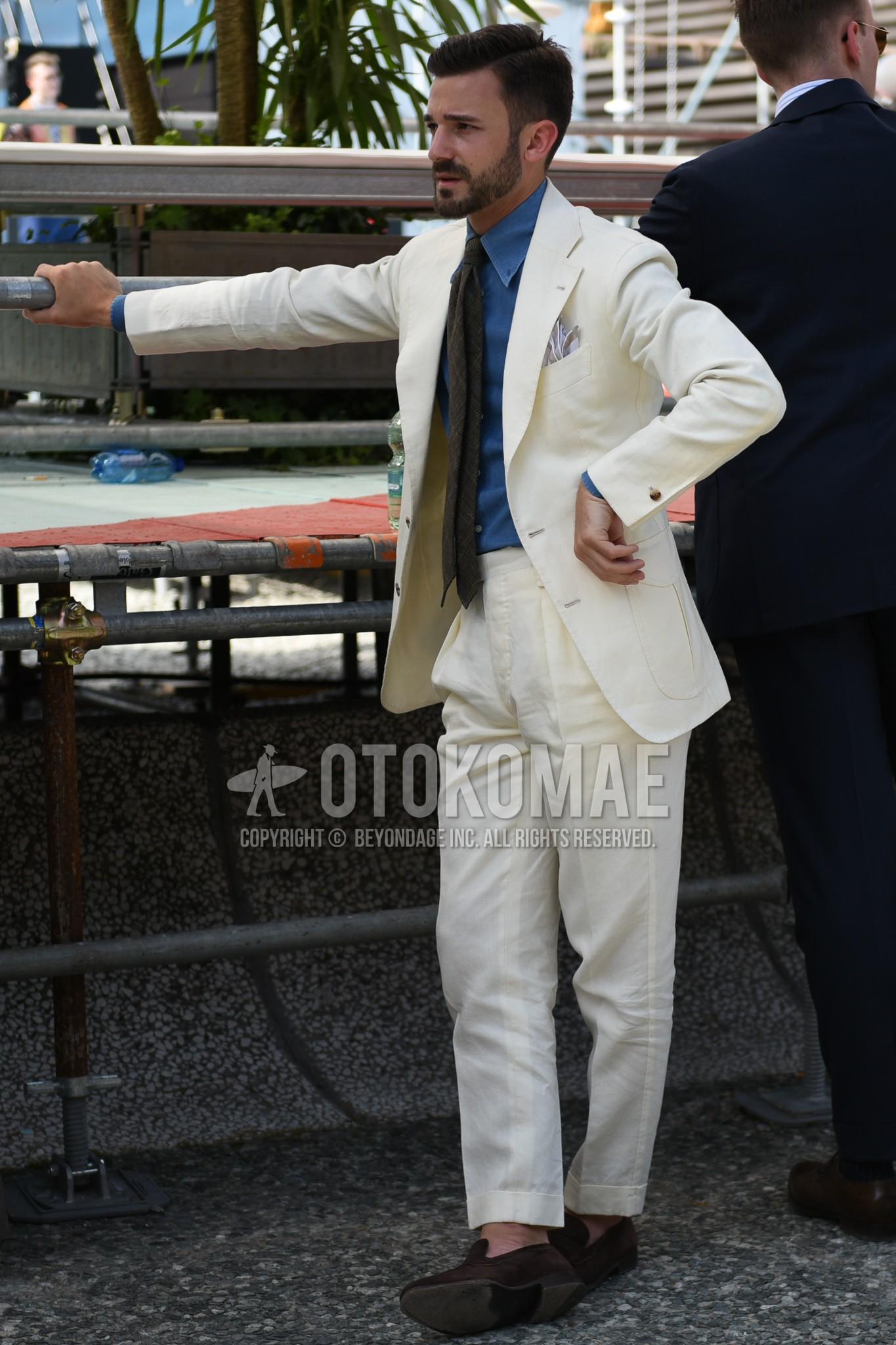 ブルー無地のデニム/シャンブレーシャツ、ブラウンローファーの革靴、白無地のスーツ、ダークグレー無地のネクタイを合わせた春夏秋のメンズコーデ・着こなし。