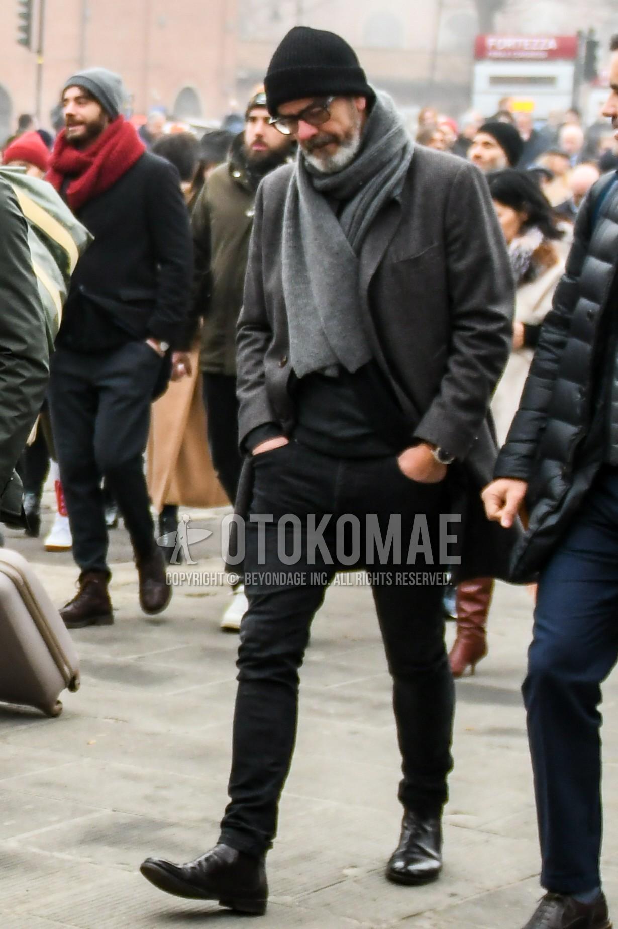 黒無地のニットキャップ、無地のメガネ、ダークグレー無地のマフラー/ストール、ダークグレー無地のチェスターコート、黒無地のセーター、黒無地のデニム/ジーンズ、黒無地のスキニーパンツ、黒サイドゴアのブーツを合わせた冬のメンズコーデ・着こなし。
