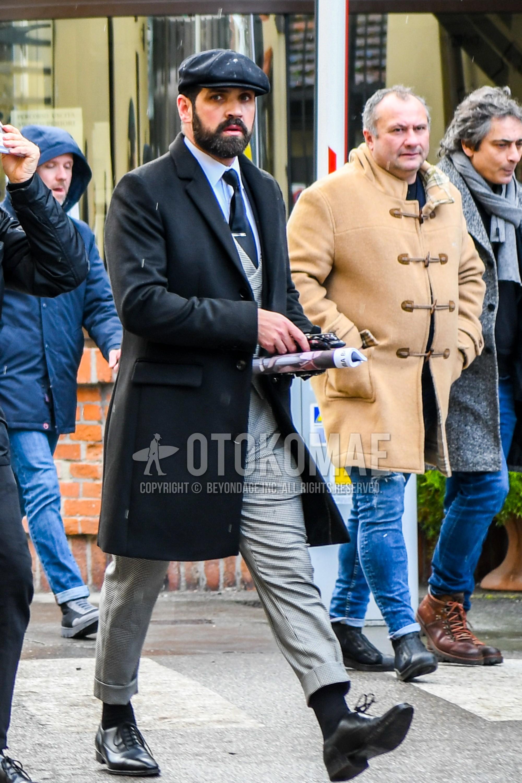 黒無地のキャップ、黒無地のチェスターコート、白無地のシャツ、黒無地のソックス、黒プレーントゥの革靴、グレー無地のスリーピーススーツ、ネイビー無地のネクタイを合わせた冬のメンズコーデ・着こなし。