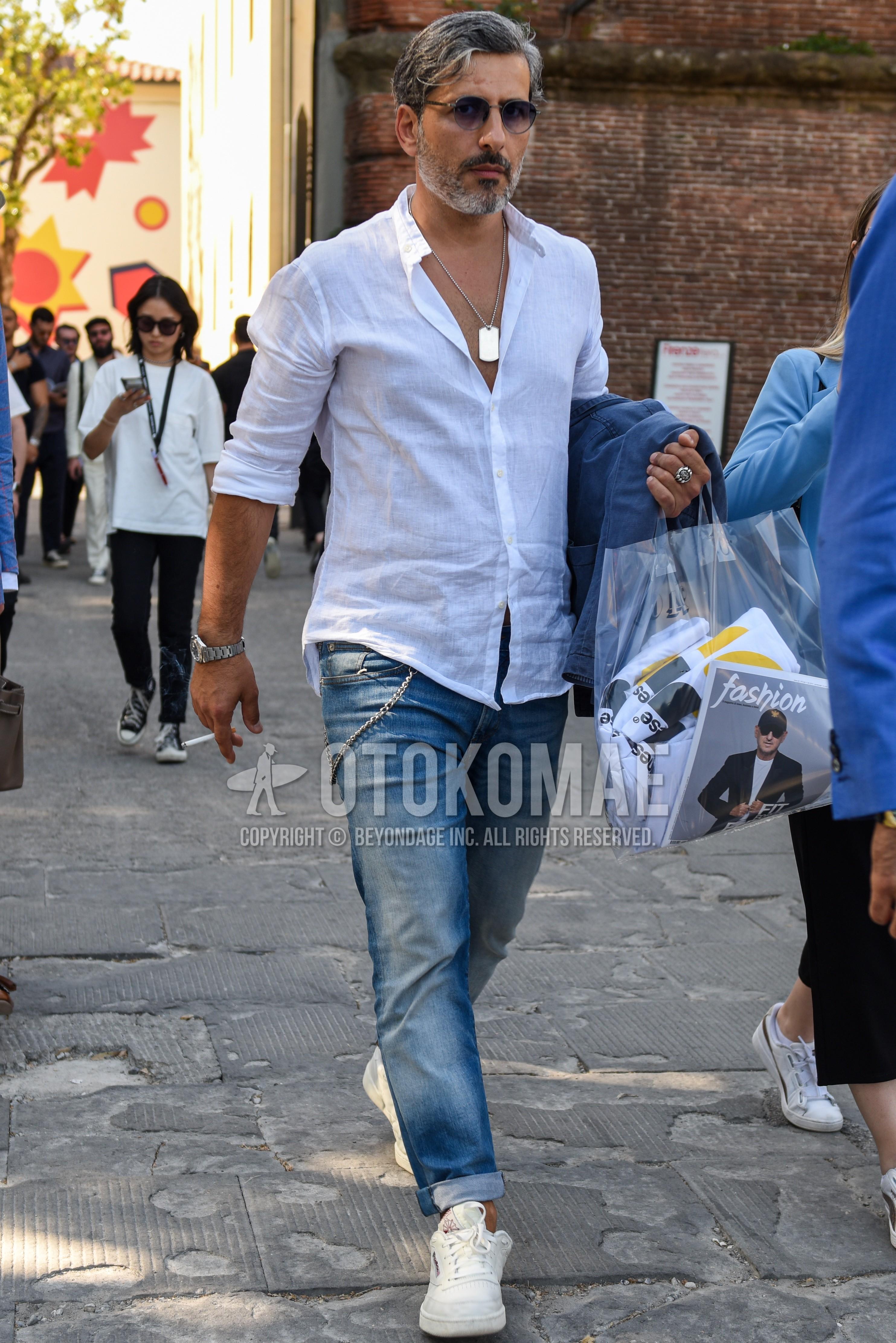 黒無地のサングラス、リネンの白無地のシャツ、ブルー無地のデニム/ジーンズ、白ローカットのスニーカーを合わせた夏のメンズコーデ・着こなし。