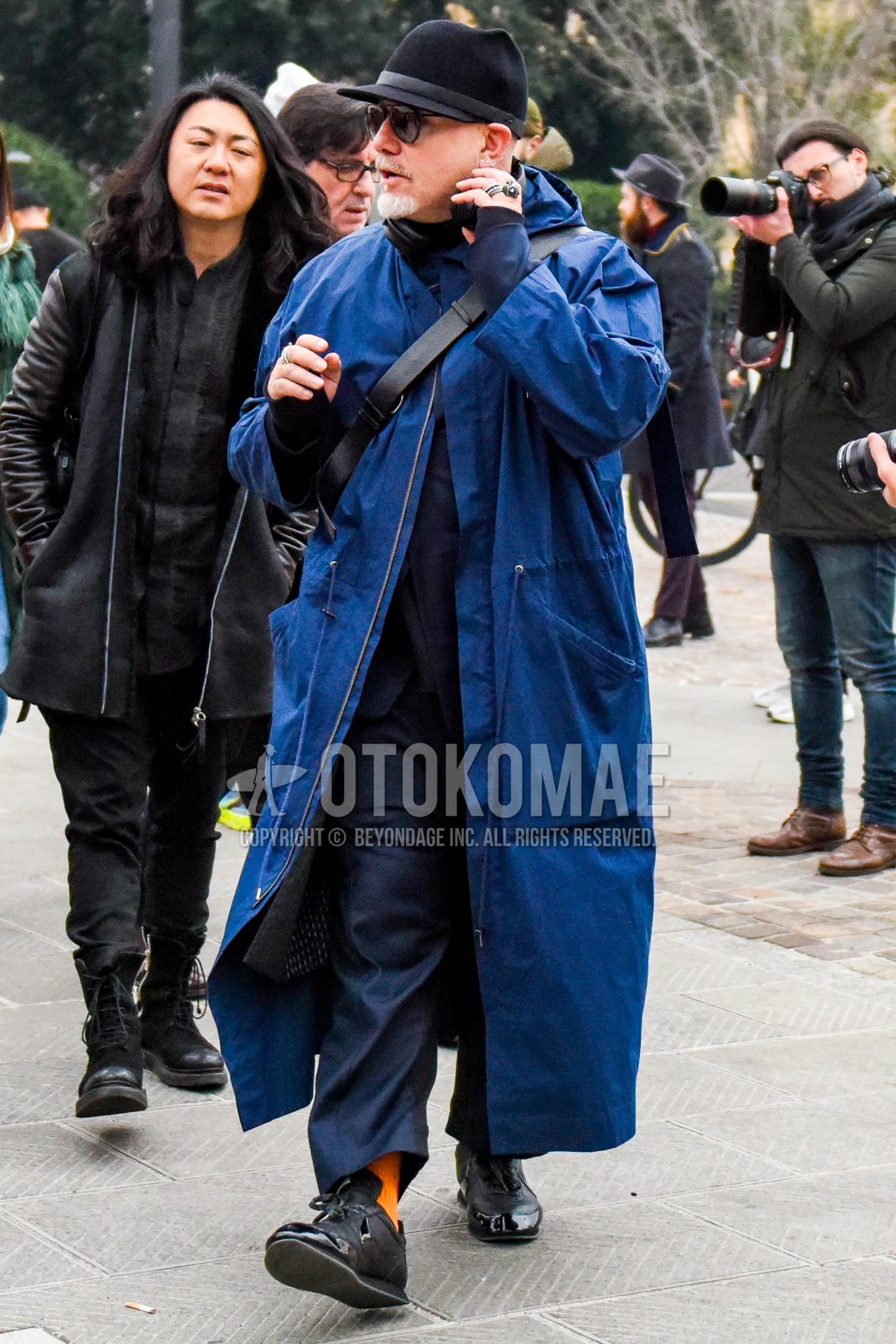 黒無地のハット、黒無地のサングラス、ブルー無地のフーデッドコート、オレンジ無地のソックス、ナイキ  コムデギャルソン ブラックの黒ローカットのスニーカー、黒無地のショルダーバッグ、ネイビー無地のスーツを合わせた秋冬のメンズコーデ・着こなし。