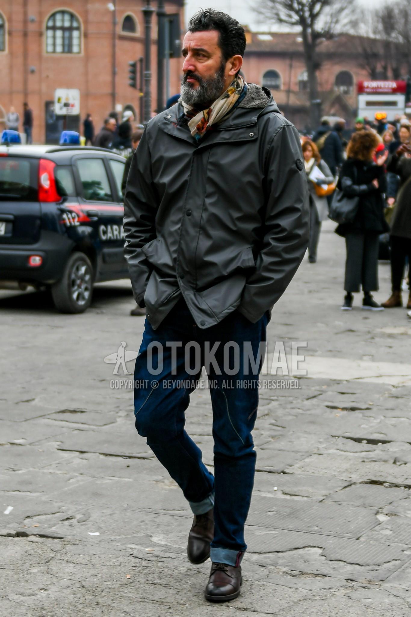 マルチカラーストールのマフラー/ストール、黒無地のフーデッドコート、ブルー無地のデニム/ジーンズ、ブラウンストレートチップの革靴を合わせた秋冬のメンズコーデ・着こなし。