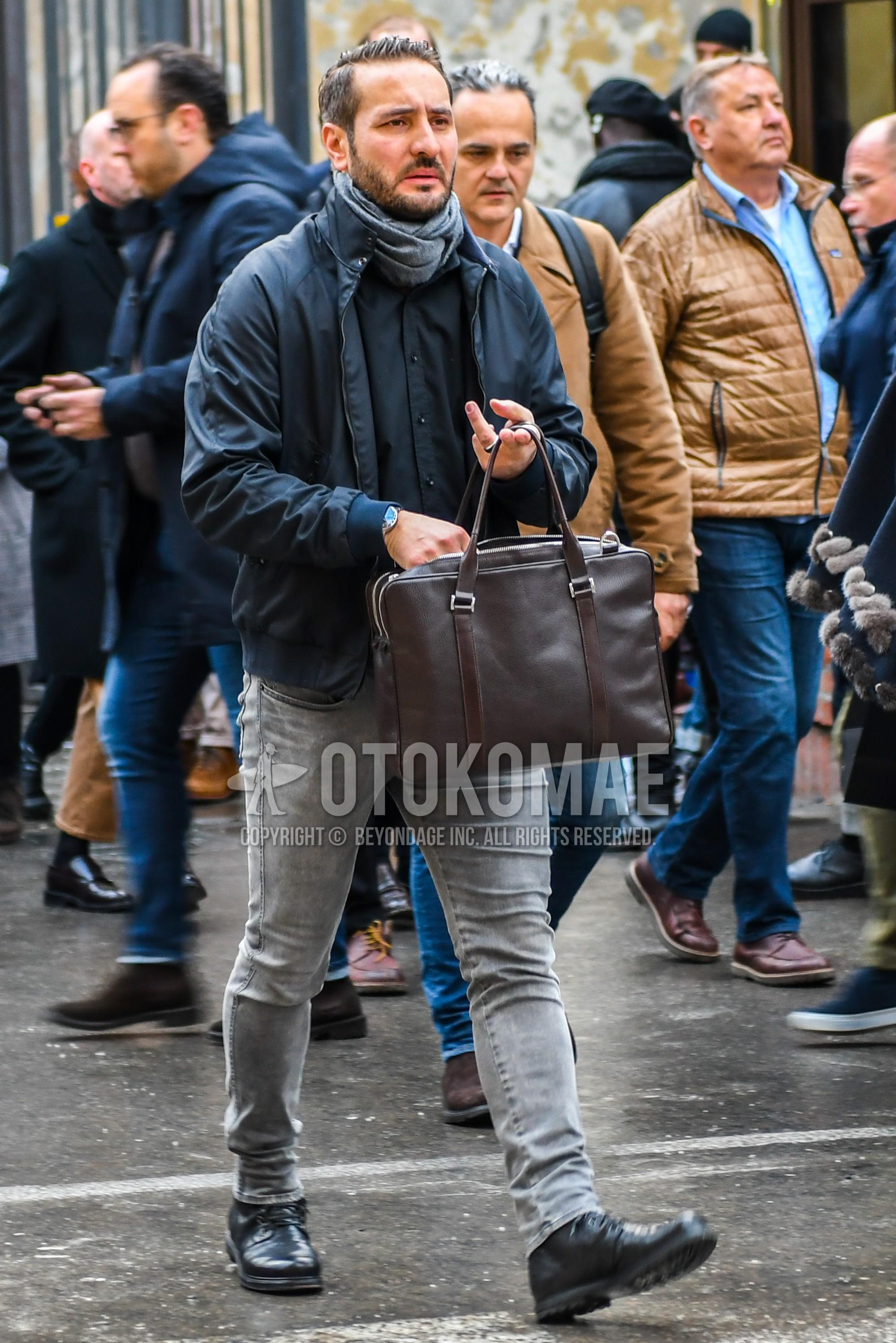グレー無地のマフラー/ストール、黒無地のアウター、黒無地のシャツ、グレー無地のデニム/ジーンズ、黒のブーツ、ブラウン無地のブリーフケース/ハンドバッグを合わせた冬のメンズコーデ・着こなし。