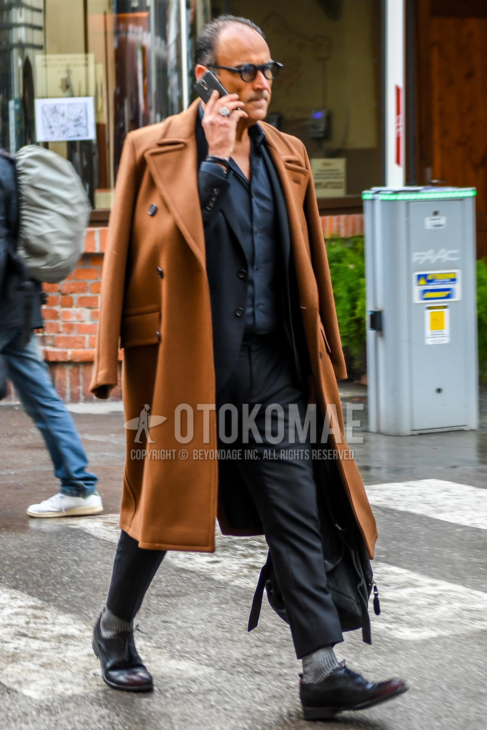黒無地のメガネ、ブラウン無地のアルスターコート、ダークグレー無地のシャツ、グレー無地のソックス、ブラウンストレートチップの革靴、ダークグレー無地のスーツを合わせた冬のメンズコーデ・着こなし。