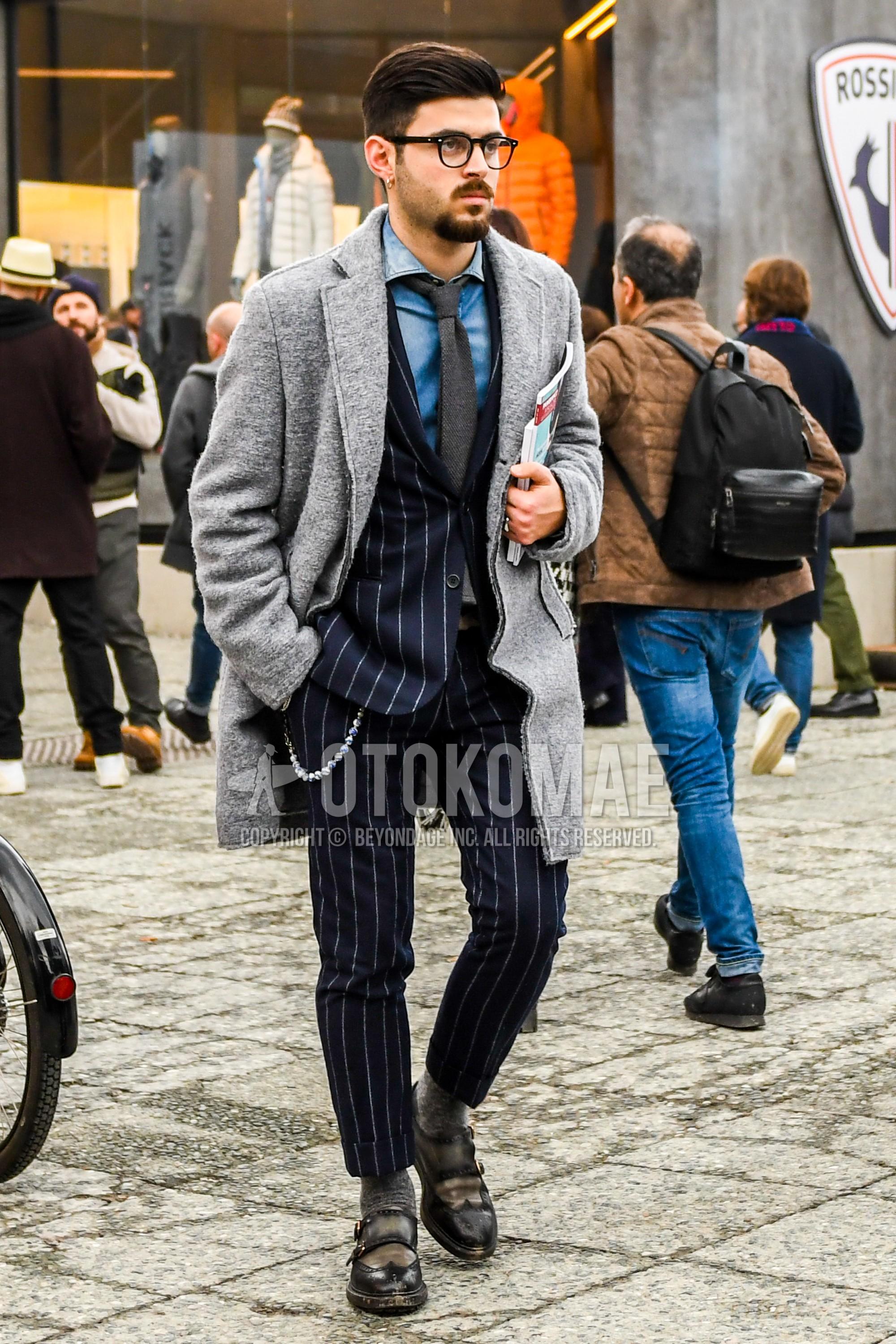 無地のメガネ、グレー無地のチェスターコート、ブルー無地のデニム/シャンブレーシャツ、グレー無地のソックス、ブラウンモンクシューズの革靴、ネイビーストライプのスーツ、ダークグレー無地のネクタイを合わせた冬のメンズコーデ・着こなし。