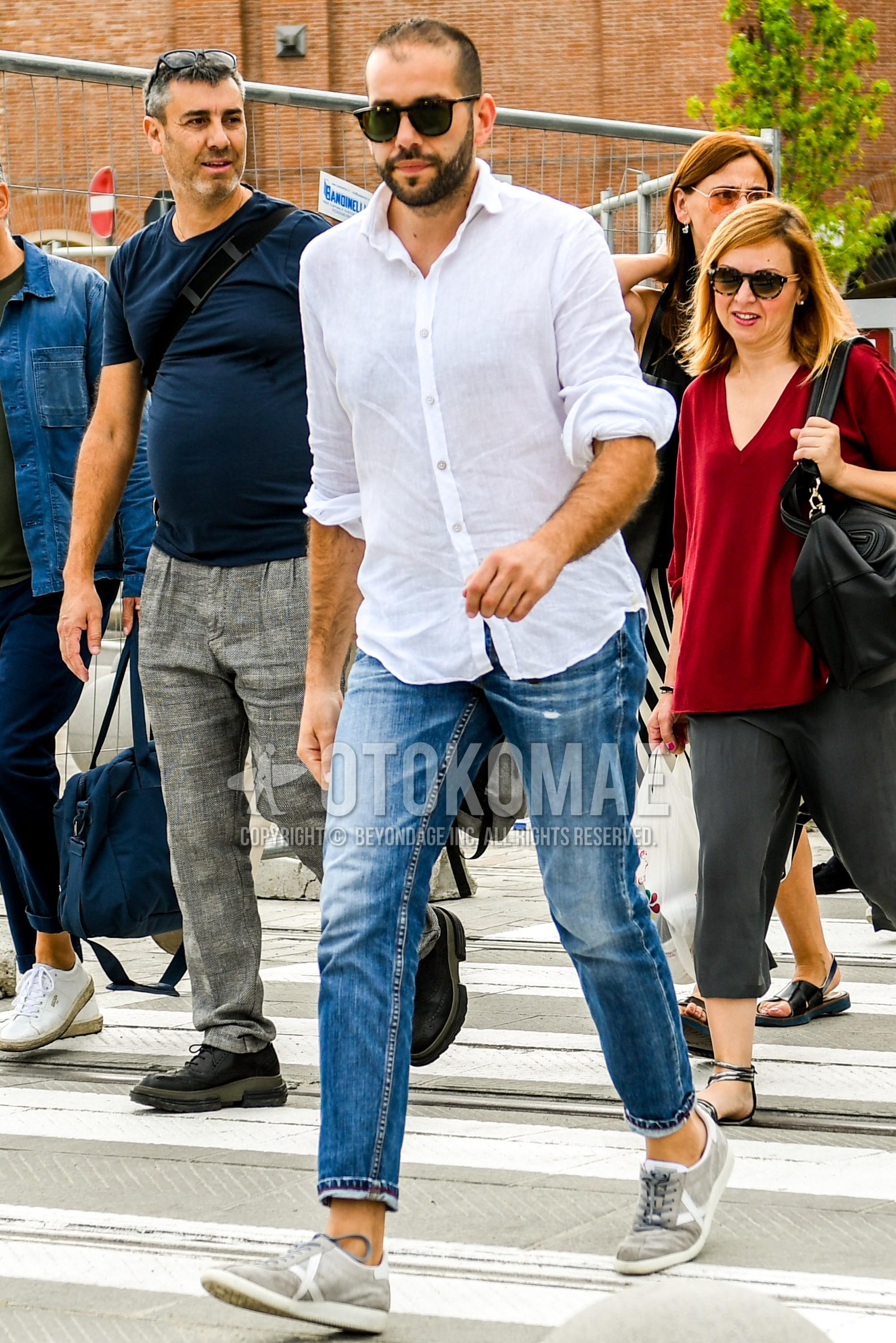 ブラウンべっ甲のサングラス、白無地のシャツ、ブルー無地のデニム/ジーンズ、グレーローカットのスニーカーを合わせた春夏のメンズコーデ・着こなし。