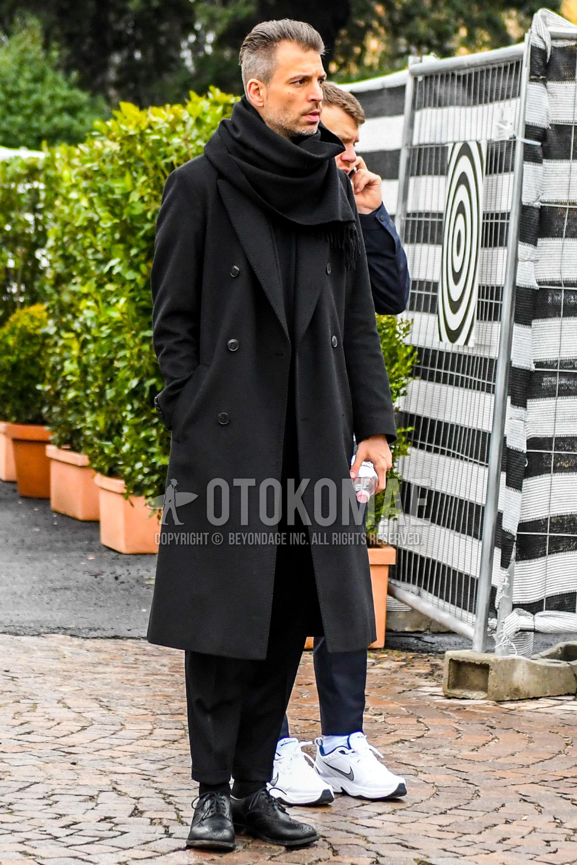 黒無地のマフラー/ストール、黒無地のチェスターコート、黒無地のセーター、黒無地のソックス、黒ウィングチップの革靴、黒無地のスーツを合わせた秋冬のメンズコーデ・着こなし。