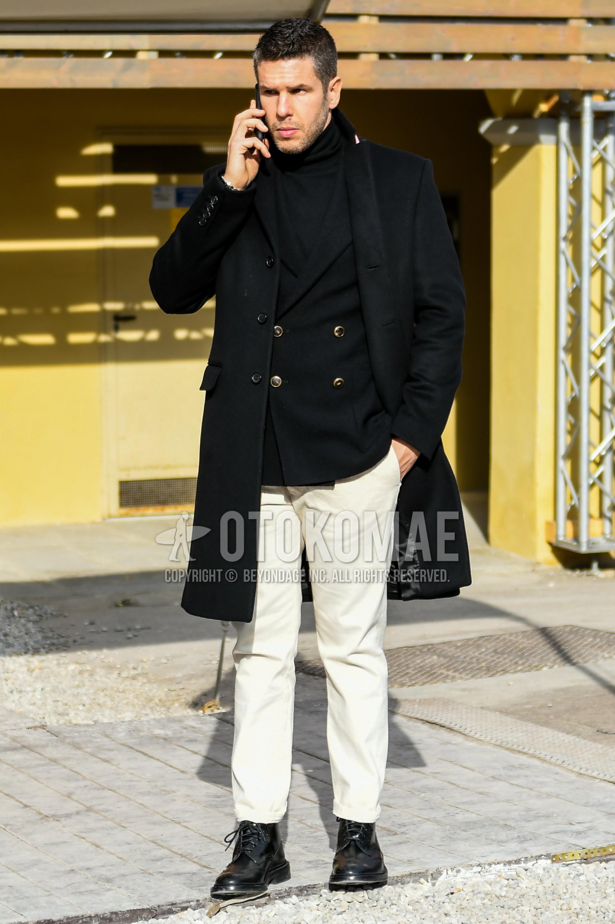 黒無地のチェスターコート、黒無地のテーラードジャケット、黒無地のタートルネックニット、白無地のコットンパンツ、黒のブーツを合わせた冬のメンズコーデ・着こなし。