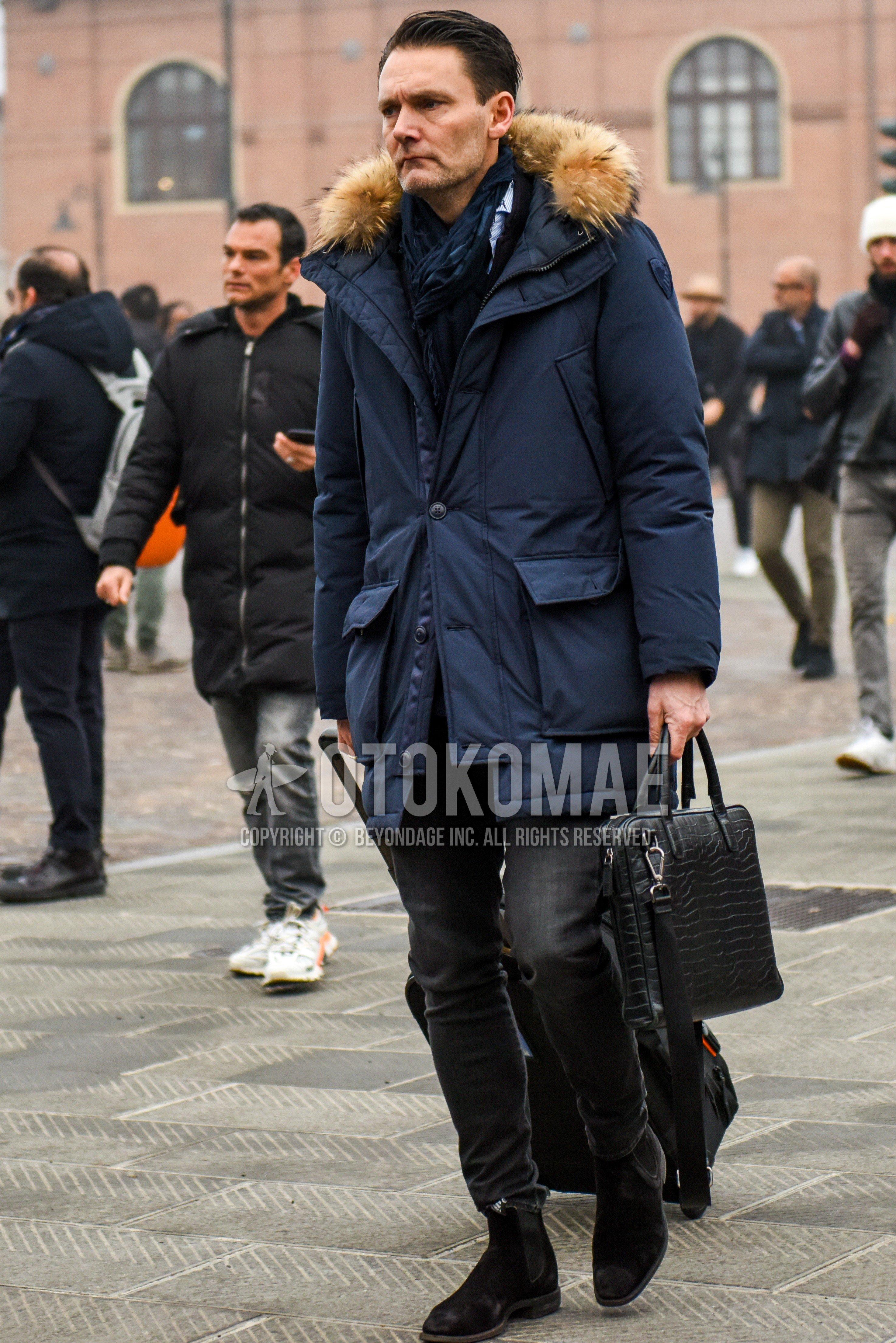 ネイビー無地のマフラー/ストール、ネイビー無地のダウンジャケット、白・水色ストライプのシャツ、グレー無地のデニム/ジーンズ、ブラウンサイドゴアのブーツ、スエードシューズの革靴、黒無地のブリーフケース/ハンドバッグを合わせた冬のメンズコーデ・着こなし。