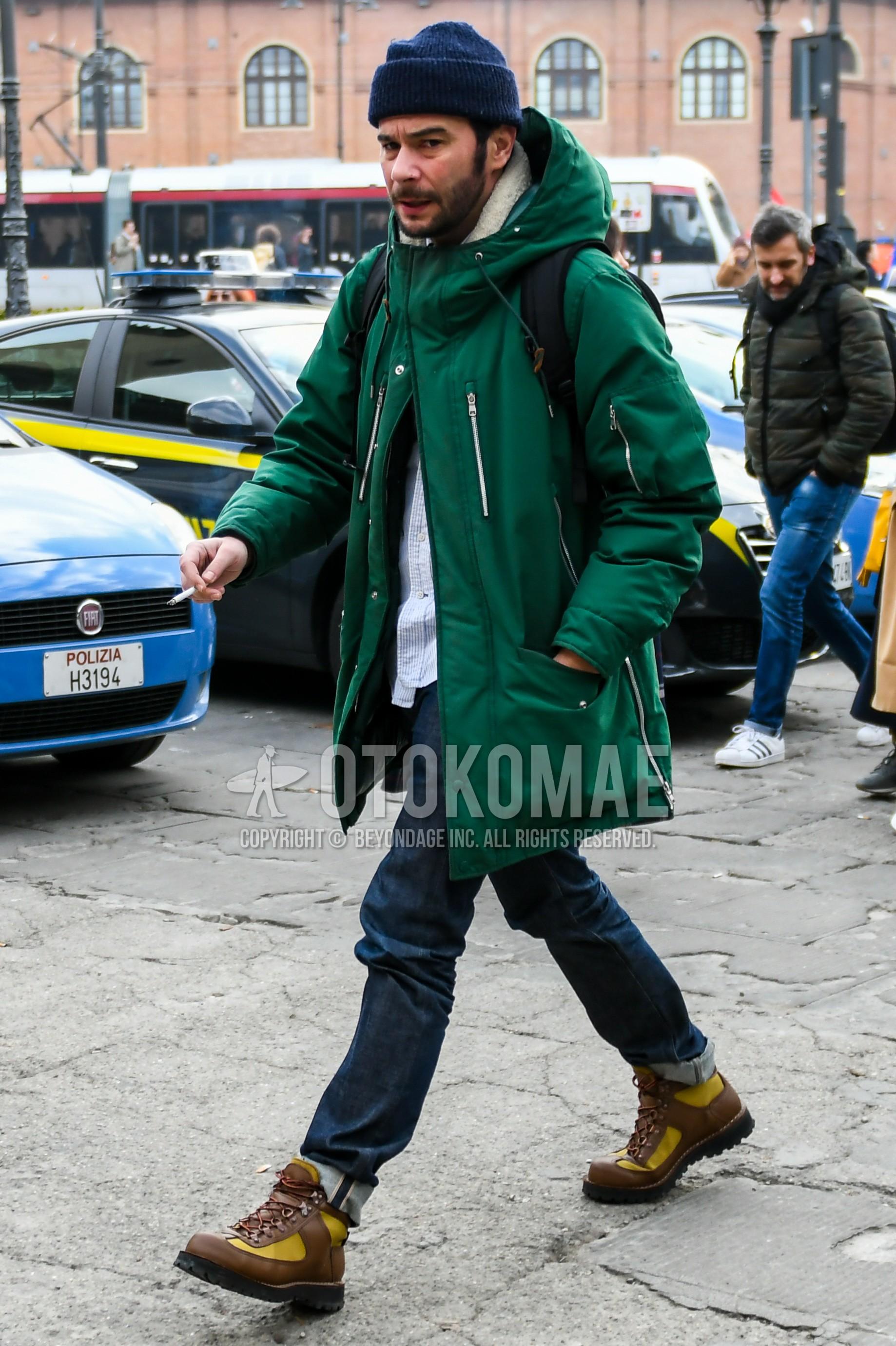 ネイビー無地のニットキャップ、グリーン無地のダウンジャケット、白ストライプのシャツ、ネイビー無地のデニム/ジーンズ、ブラウンのブーツを合わせた冬のメンズコーデ・着こなし。
