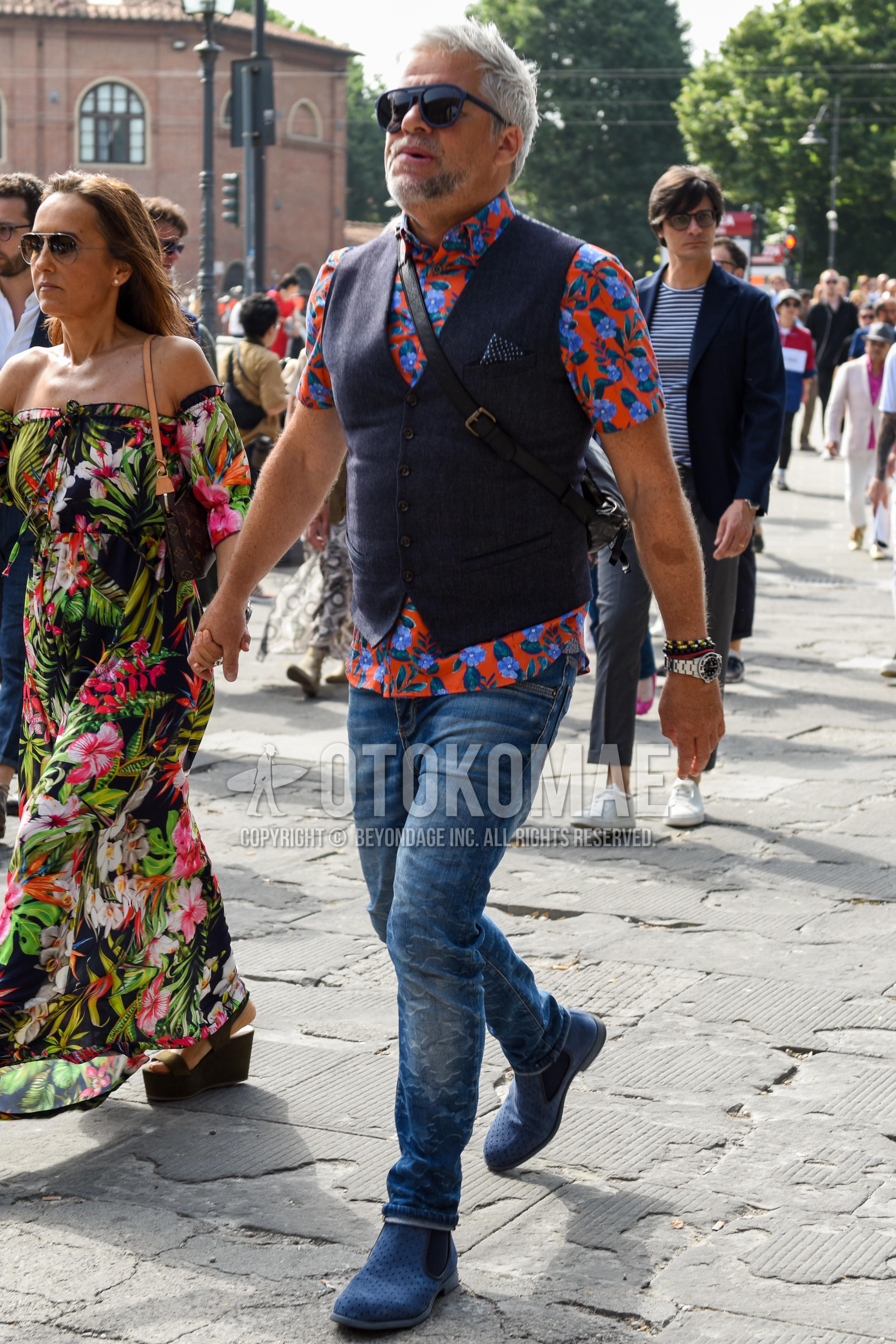 黒無地のサングラス、レッド・ブルートップス/インナーのTシャツ、ダークグレー無地のジレ、ブルー無地のデニム/ジーンズ、ブルーサイドゴアのブーツを合わせた夏のメンズコーデ・着こなし。