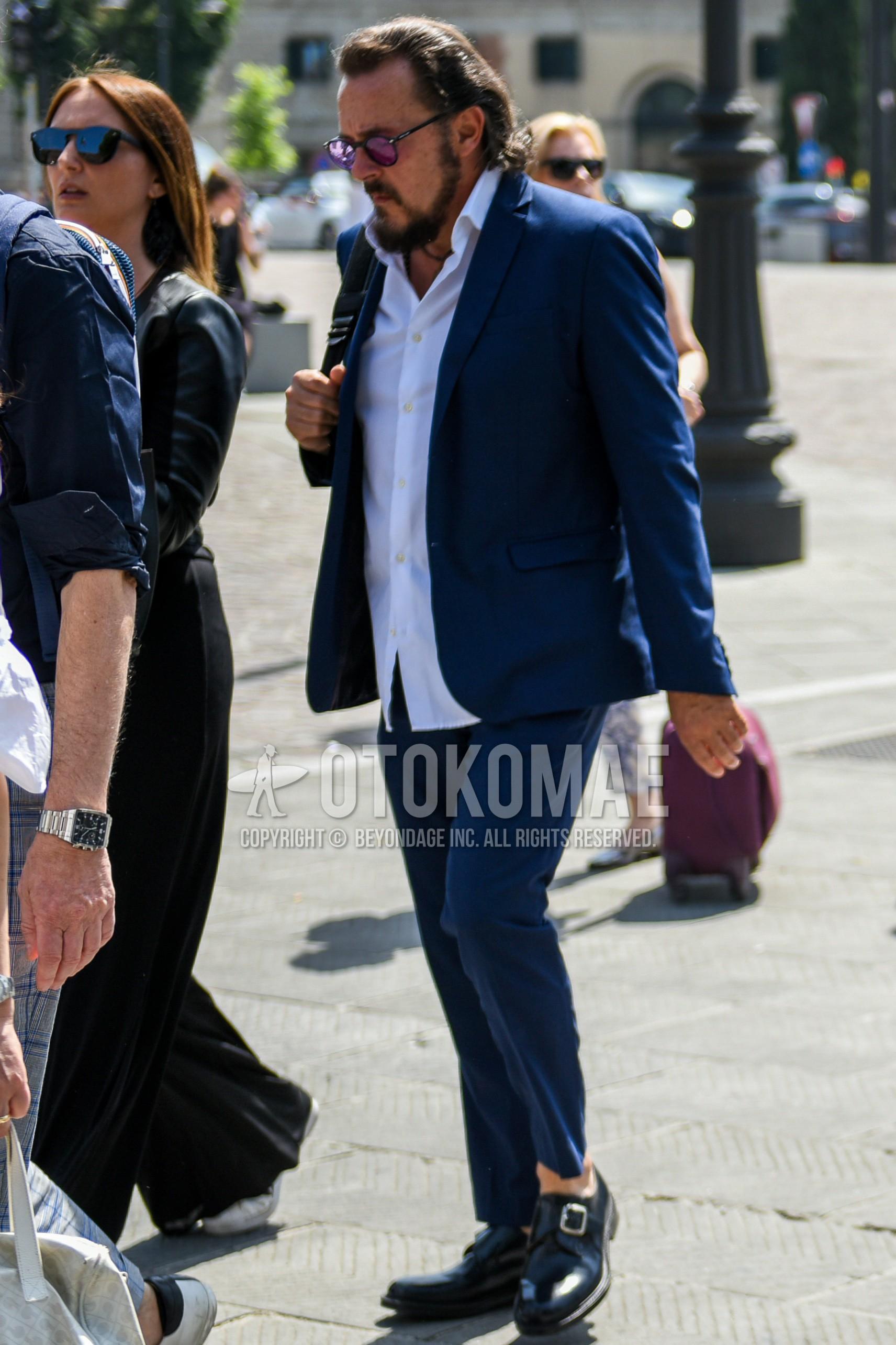 黒無地のサングラス、白無地のシャツ、黒モンクシューズの革靴、ネイビー無地のスーツを合わせた春秋のメンズコーデ・着こなし。
