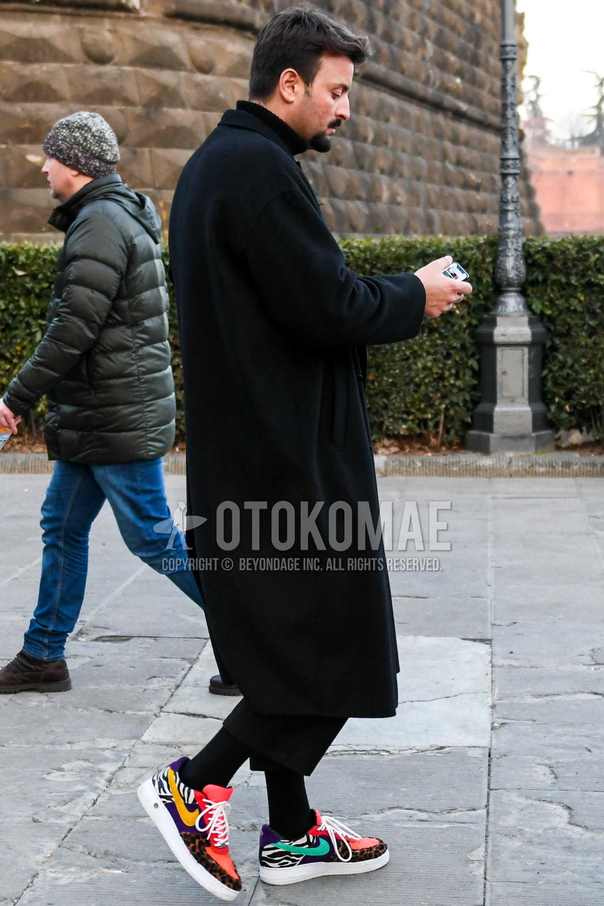 黒無地のチェスターコート、黒無地のタートルネックニット、黒無地のアンクルパンツ、黒無地のソックス、マルチカラーローカットのスニーカーを合わせた冬のメンズコーデ・着こなし。
