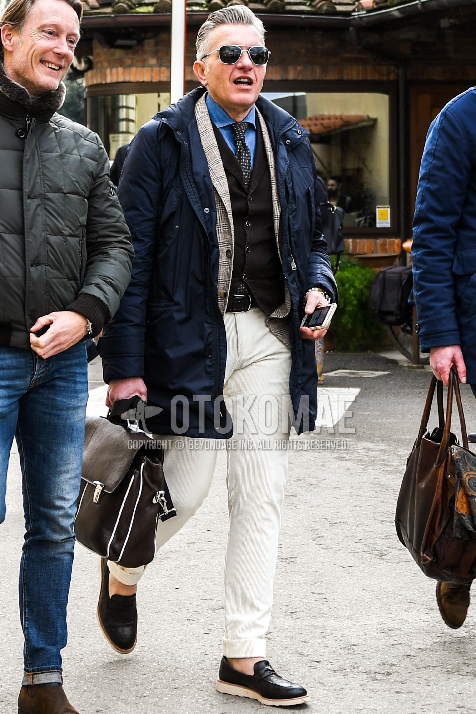 シルバー無地のサングラス、ネイビー無地のフーデッドコート、グレンチェックのグレーチェックのテーラードジャケット、黒無地のジレ、ブルー無地のデニム/シャンブレーシャツ、黒無地のメッシュベルト、白無地のコットンパンツ、黒コインローファーの革靴、ブラウン無地のブリーフケース/ハンドバッグを合わせた冬のメンズコーデ・着こなし。