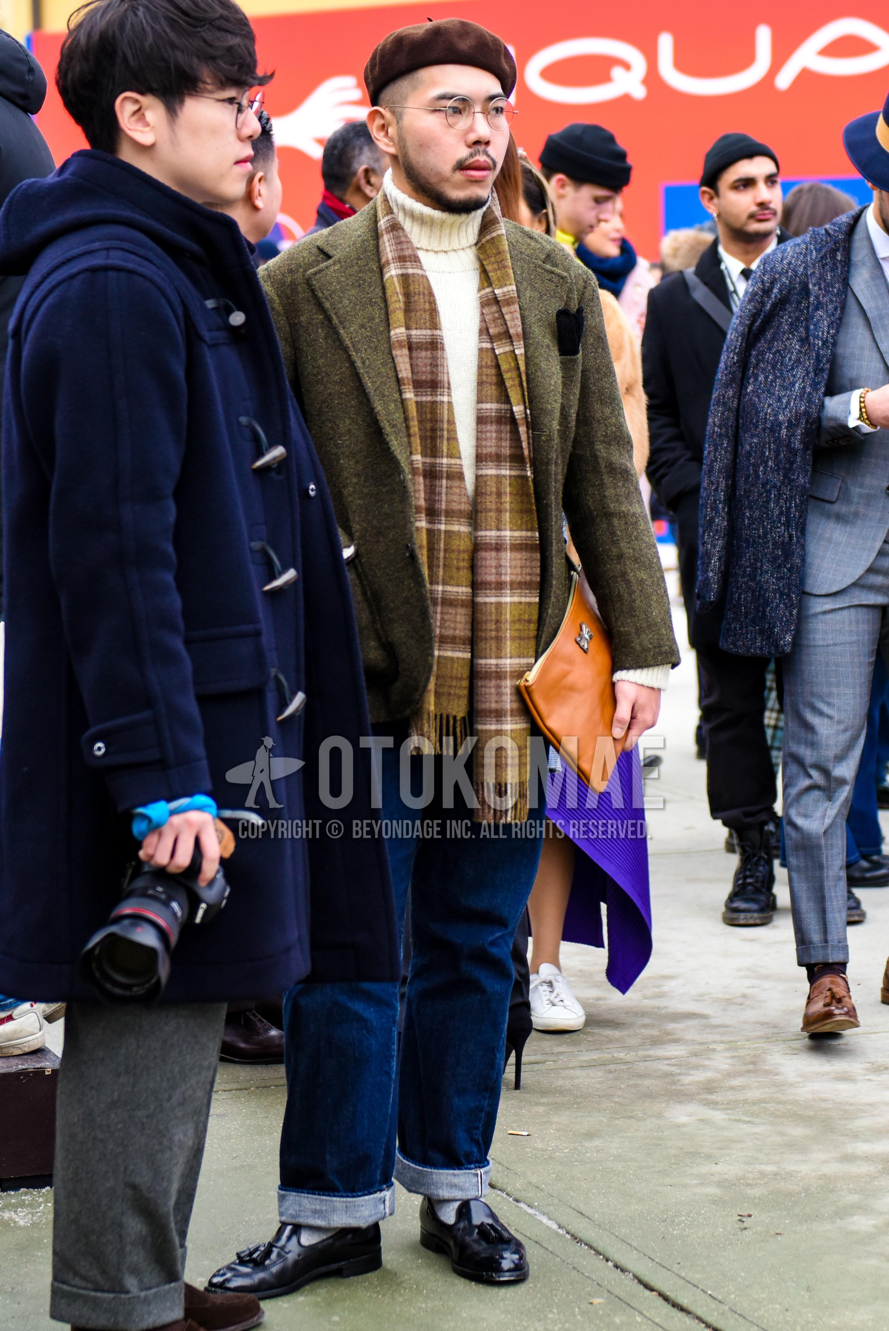 ブラウン無地のキャップ、シルバー無地のメガネ、ブラウンチェックのマフラー/ストール、オリーブグリーン無地のテーラードジャケット、白無地のタートルネックニット、ブルー無地のデニム/ジーンズ、グレー無地のソックス、黒タッセルローファーの革靴、ベージュ無地のクラッチバッグ/セカンドバッグ/巾着を合わせた秋冬のメンズコーデ・着こなし。