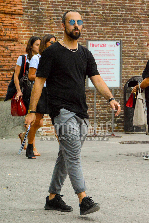 シルバー無地のサングラス、黒無地のTシャツ、グレー無地のコットンパンツ、黒ローカットのスニーカーを合わせた夏のメンズコーデ・着こなし。