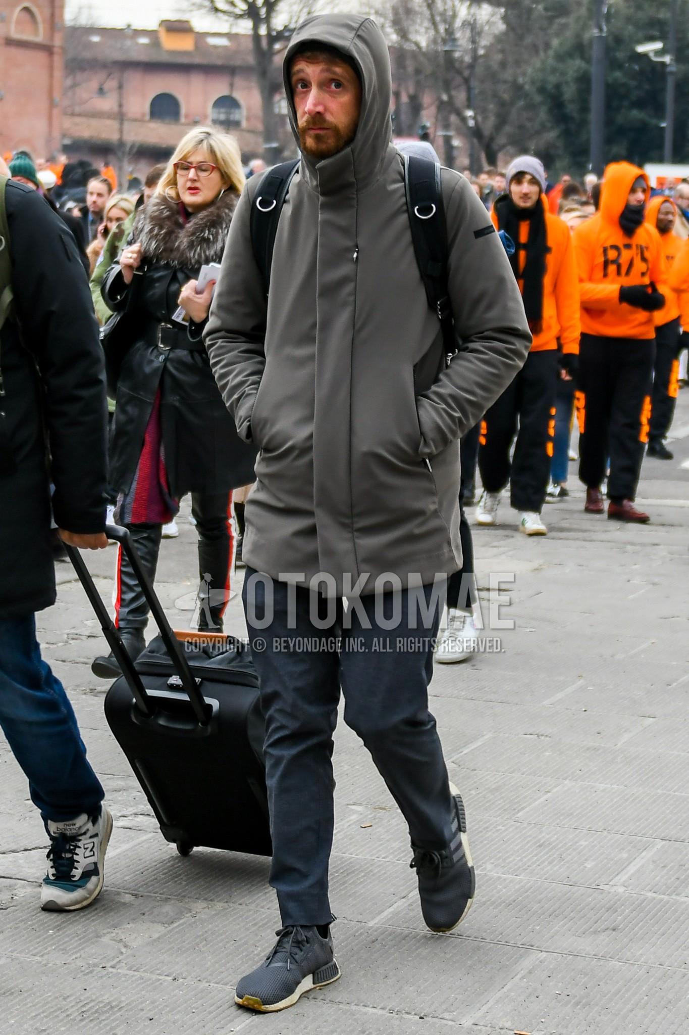 グレー無地のフーデッドコート、ネイビー無地のチノパン、アディダス NMDのグレーローカットのスニーカー、黒無地のバックパックを合わせた秋冬のメンズコーデ・着こなし。