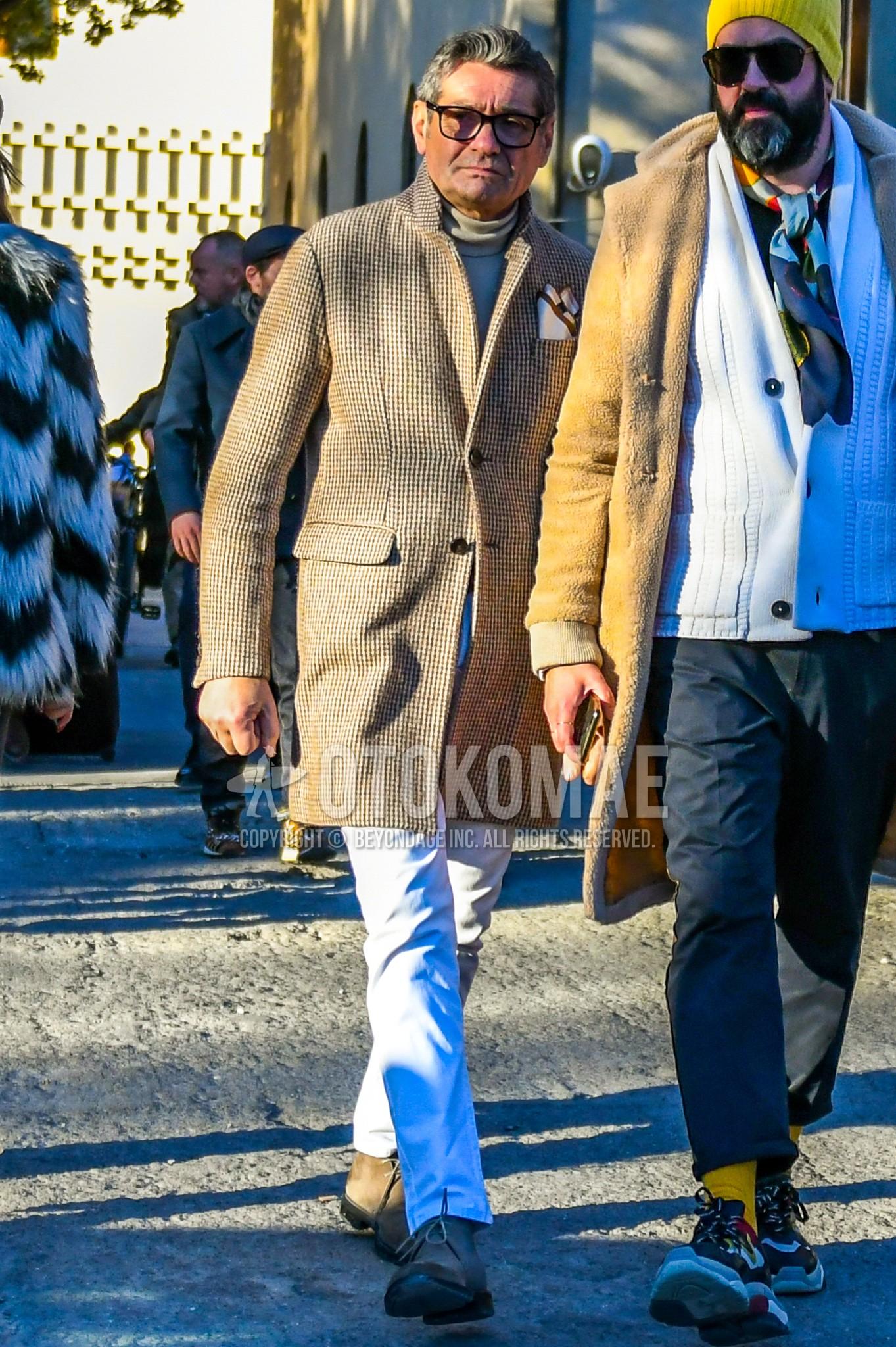 黒無地のメガネ、ベージュチェックのチェスターコート、ベージュ無地のタートルネックニット、白無地のデニム/ジーンズ、スエードのベージュチャッカのブーツを合わせた秋冬のメンズコーデ・着こなし。