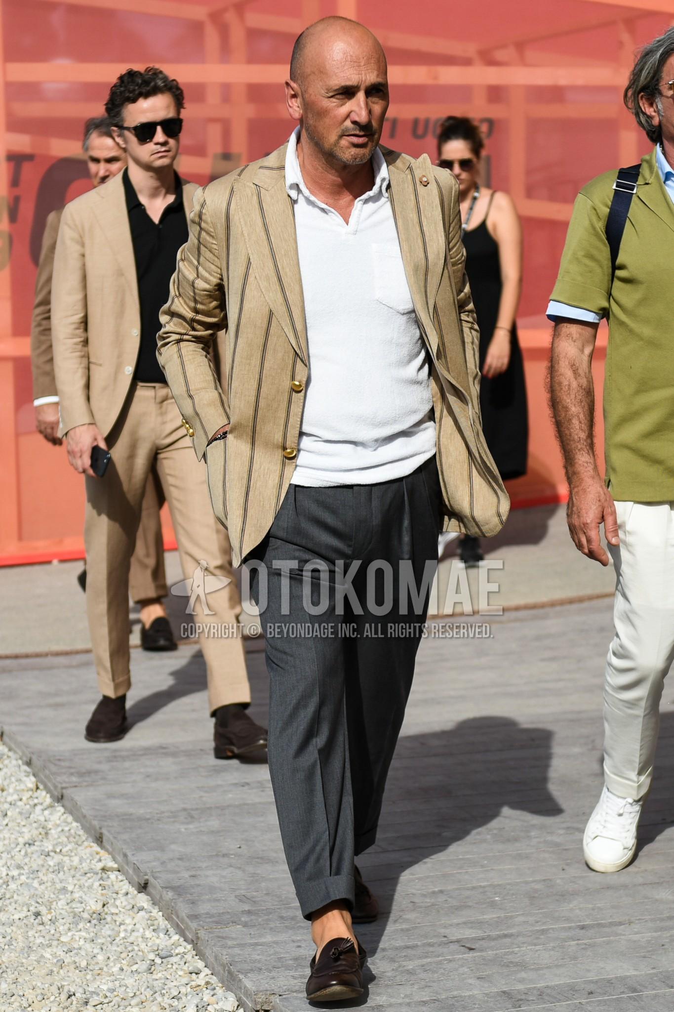 ベージュストライプのテーラードジャケット、白無地のポロシャツ、グレー無地のスラックス、ブラウンタッセルローファーの革靴を合わせた春夏秋のメンズコーデ・着こなし。