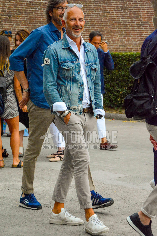 クリア無地のサングラス、ブルー無地のデニムジャケット、白無地のシャツ、ブラウン無地のレザーベルト、ベージュ無地のチノパン、ゴールデングースの白ローカットのスニーカーを合わせた春秋のメンズコーデ・着こなし。