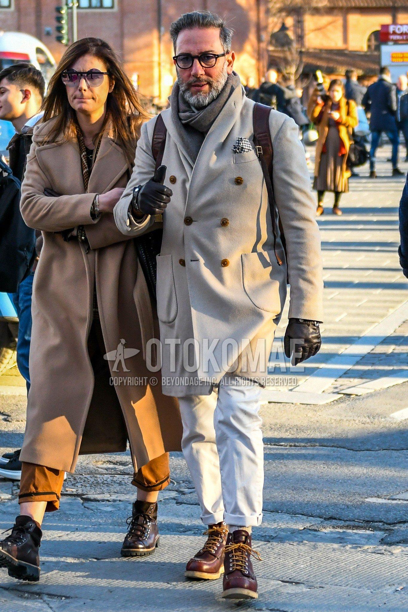 無地のメガネ、グレー無地のマフラー/ストール、ベージュ無地のチェスターコート、白無地のコットンパンツ、ブラウンワークのブーツを合わせたメンズコーデ・着こなし。