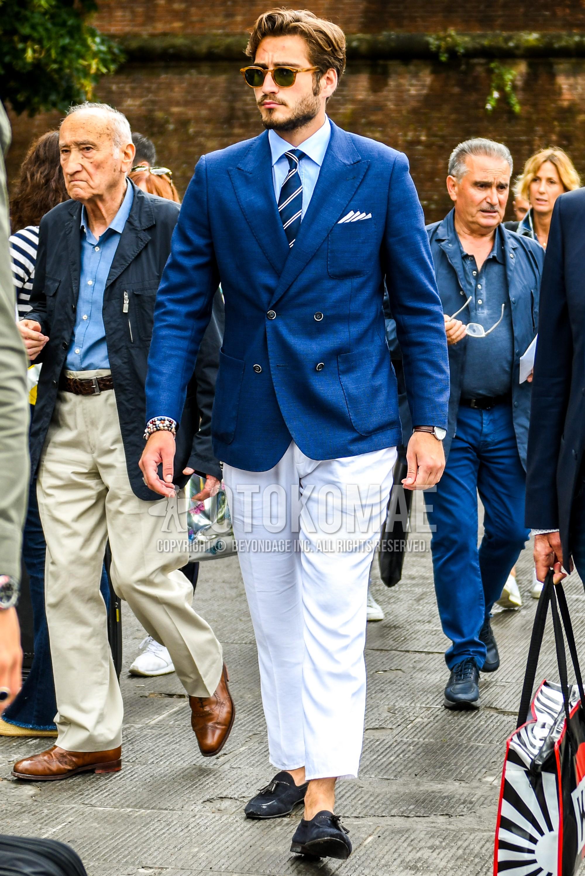 ベージュべっ甲のサングラス、ブルー無地のテーラードジャケット、水色無地のシャツ、白無地のコットンパンツ、白無地のアンクルパンツ、スエードのネイビータッセルローファーの革靴、ネイビーレジメンタルのネクタイを合わせた春秋のメンズコーデ・着こなし。
