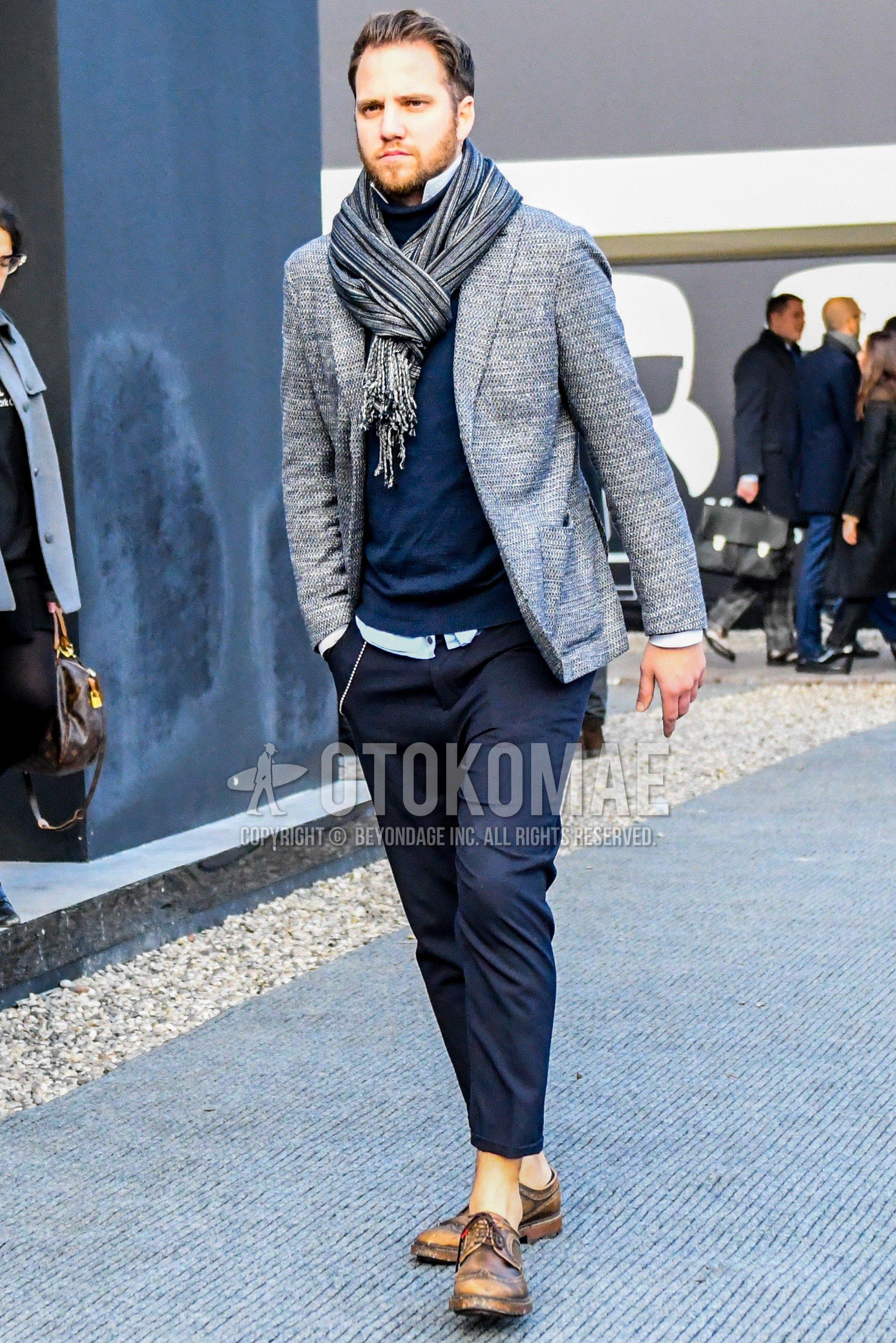 グレーストールのマフラー/ストール、グレー無地のテーラードジャケット、グレー無地のタートルネックニット、白無地のシャツ、グレー無地のスラックス、ブラウンウィングチップの革靴を合わせたメンズコーデ・着こなし。