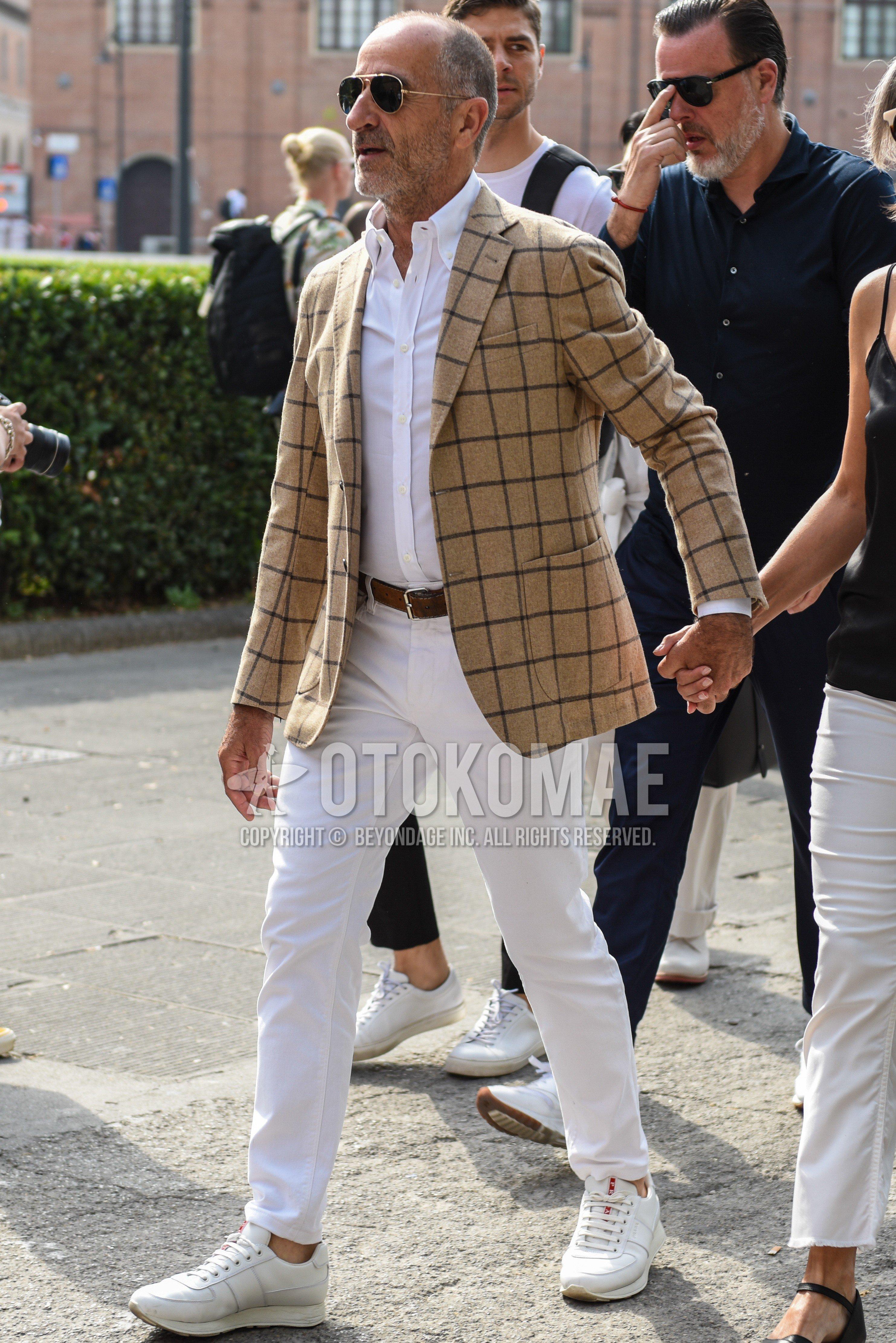 ゴールド無地のサングラス、ベージュチェックのテーラードジャケット、白無地のシャツ、ブラウン無地のレザーベルト、白無地のコットンパンツ、白ローカットのスニーカーを合わせた春夏秋のメンズコーデ・着こなし。