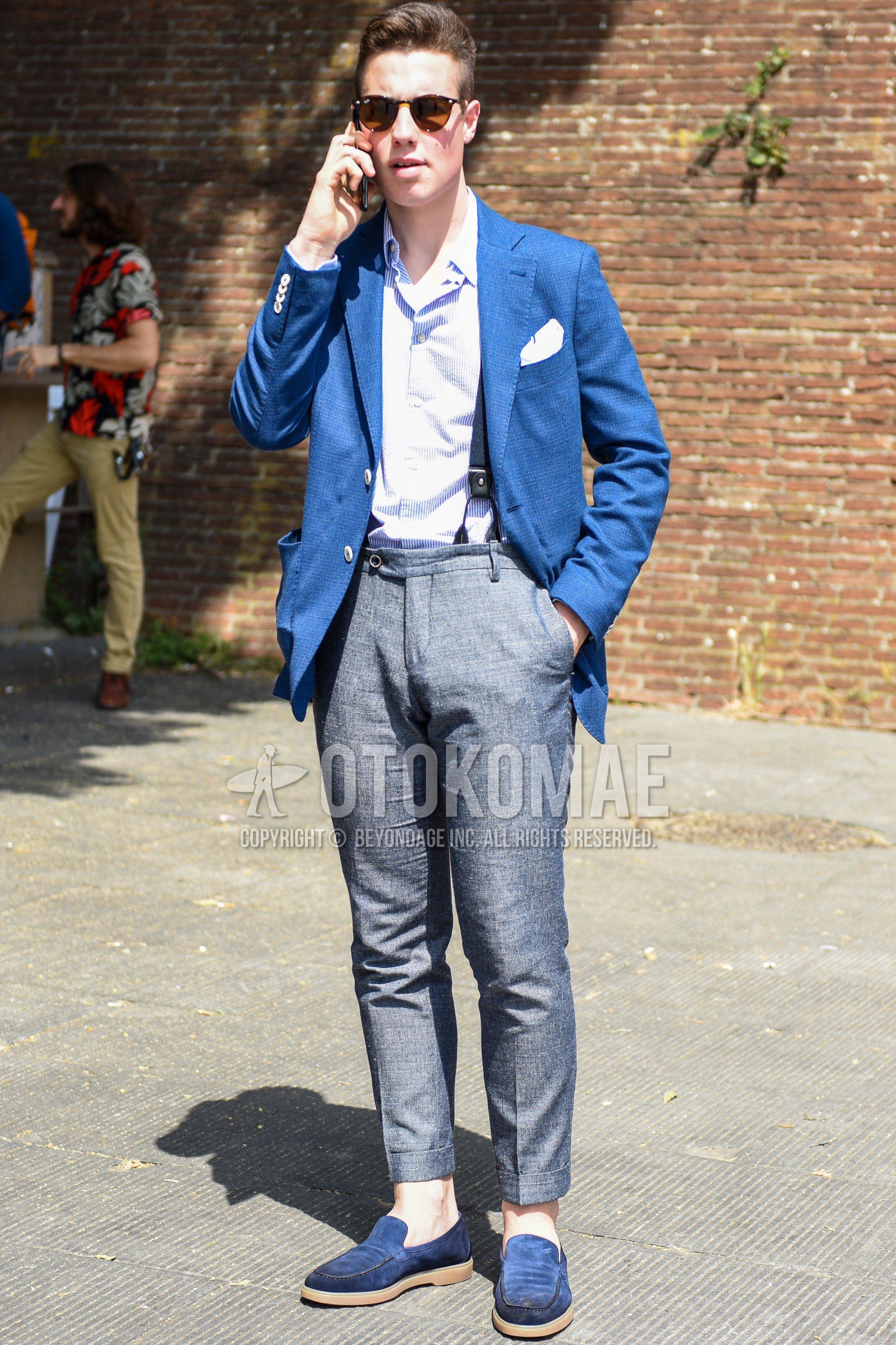 黒無地のサングラス、ブルー無地のテーラードジャケット、水色無地のシャツ、ネイビー無地のサスペンダー、グレー無地のベルトレスパンツ、ブルーローファーの革靴を合わせた春夏秋のメンズコーデ・着こなし。