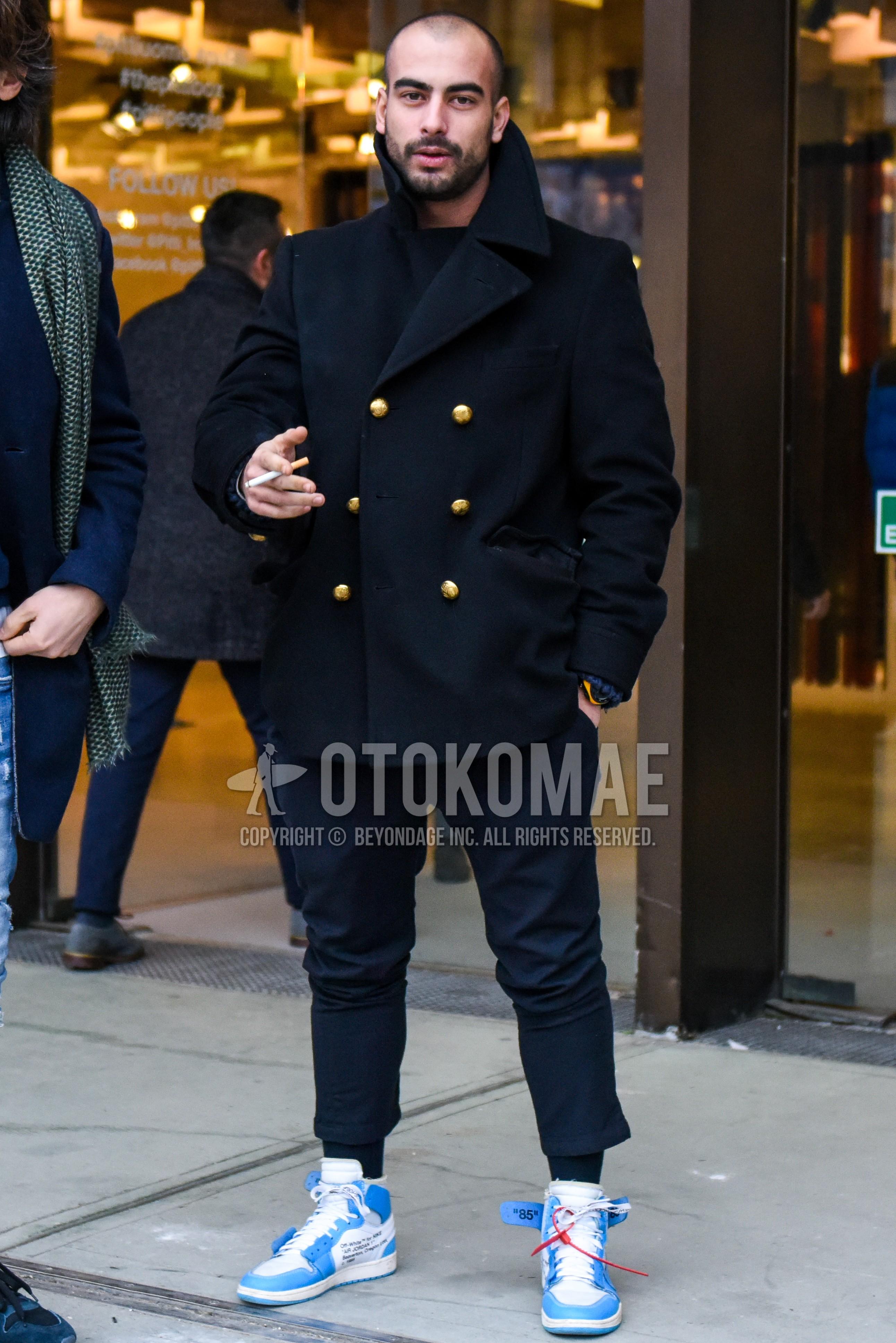 黒無地のPコート、黒無地のセーター、黒無地のスラックス、黒無地のソックス、オフホワイトの白・水色ハイカットのスニーカーを合わせた秋冬のメンズコーデ・着こなし。
