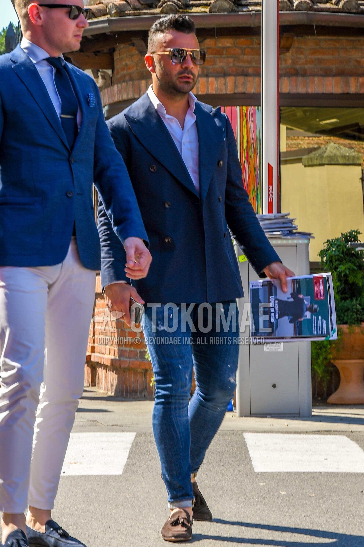 ゴールド無地のサングラス、ネイビー無地のテーラードジャケット、白無地のシャツ、ブルー無地のデニム/ジーンズ、スエードのブラウンタッセルローファーの革靴を合わせた春夏秋のメンズコーデ・着こなし。