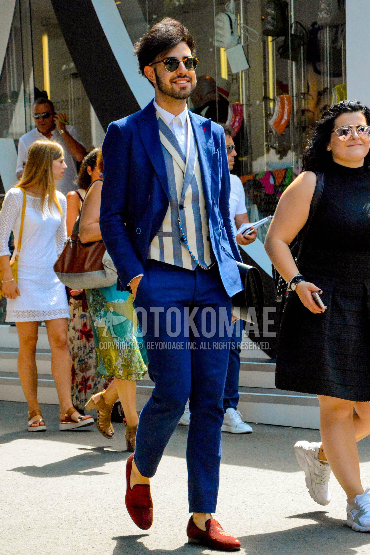 無地のサングラス、白無地のシャツ、ベージュ・水色ストライプのジレ、ブラウンモカシン/デッキシューズの革靴、ブルー無地のスーツを合わせた春夏秋のメンズコーデ・着こなし。