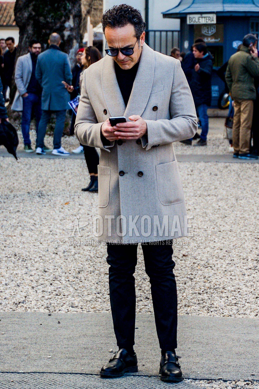 無地のサングラス、グレー無地のチェスターコート、黒無地のセーター、黒無地のスラックス、黒無地のソックス、黒モンクシューズの革靴を合わせた秋冬のメンズコーデ・着こなし。