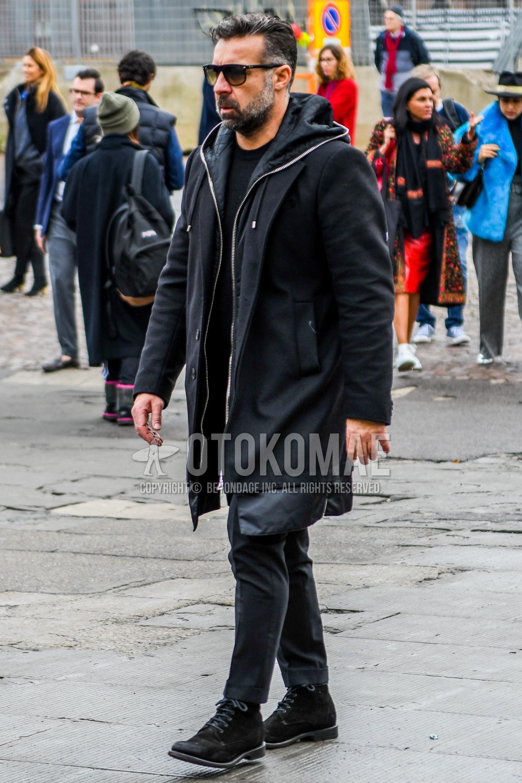 無地のサングラス、黒無地のチェスターコート、黒無地のフーディ、黒無地のセーター、ダークグレー無地のスラックス、黒のブーツを合わせた冬のメンズコーデ・着こなし。