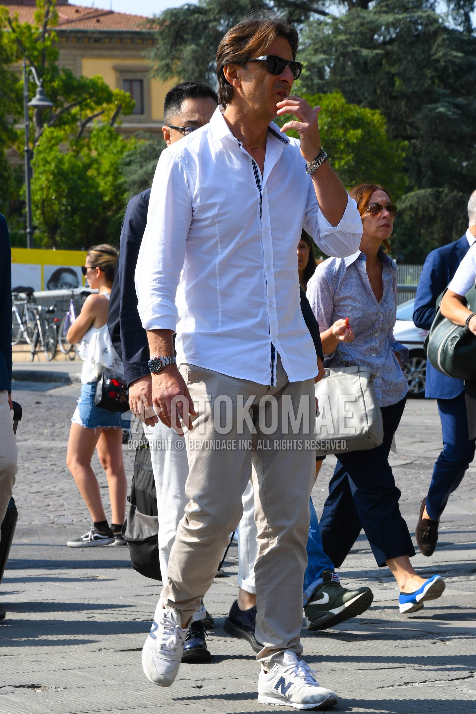 無地のサングラス、白無地のシャツ、ベージュ無地のチノパン、ニューバランスの白・グレーローカットのスニーカーを合わせた春夏のメンズコーデ・着こなし。