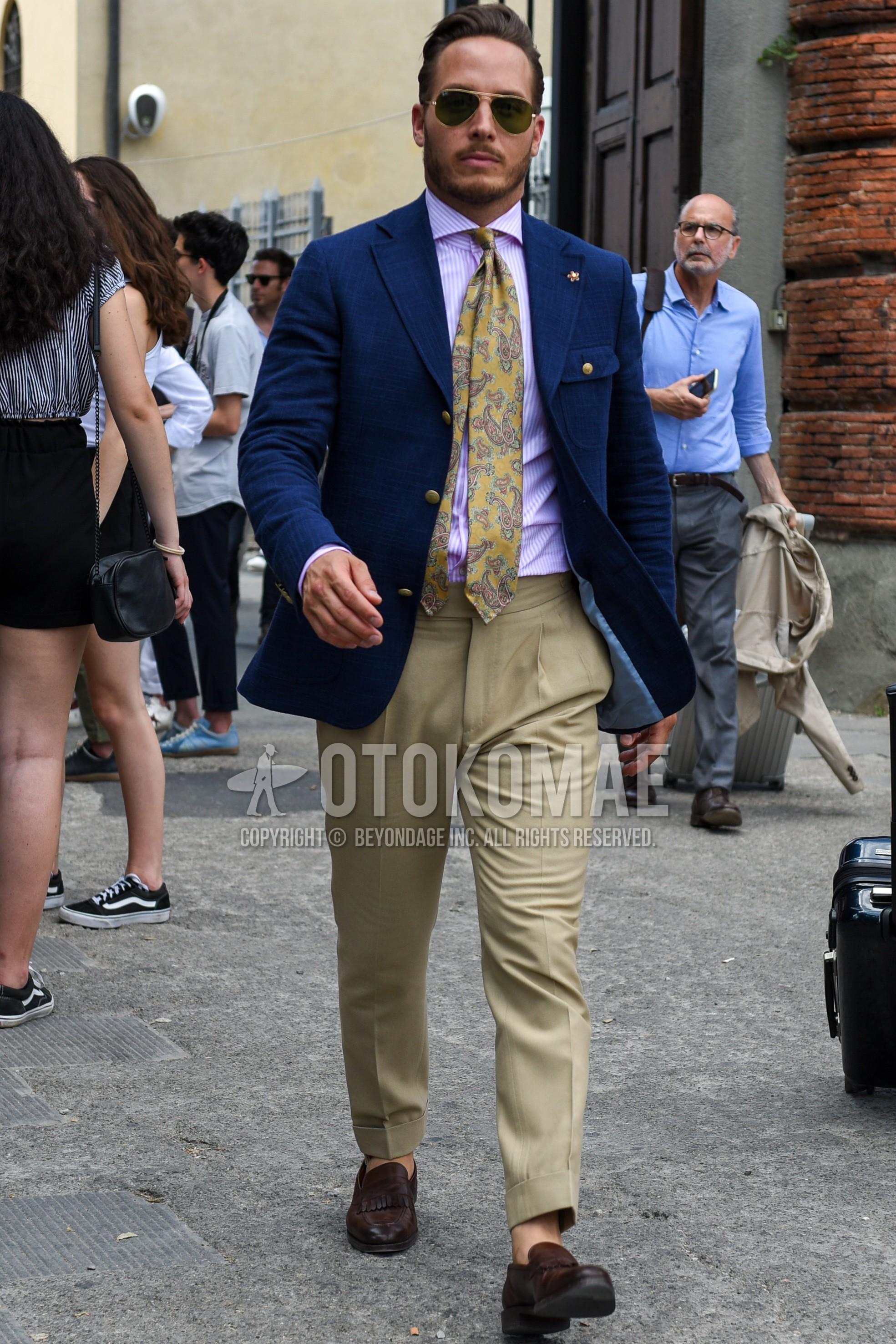ゴールド・黒無地のサングラス、ネイビー無地のテーラードジャケット、ピンク無地のシャツ、ベージュ無地のベルトレスパンツ、ブラウンコインローファーの革靴、ベージュペイズリーのネクタイを合わせた春夏秋のメンズコーデ・着こなし。