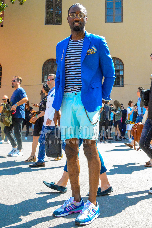 ゴールド無地のメガネ、ブルー無地のテーラードジャケット、黒・白ボーダーのTシャツ、水色無地のショートパンツ、アディダス ZXの水色ローカットのスニーカー、黒無地のクラッチバッグ/セカンドバッグ/巾着を合わせた春夏のメンズコーデ・着こなし。