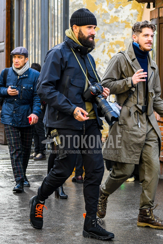 黒無地のニットキャップ、黒無地のアウター、オリーブグリーン無地のフーディ、黒無地のボトムス、黒のブーツを合わせた秋冬のメンズコーデ・着こなし。