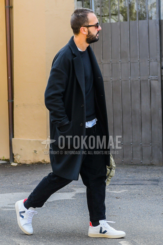 黒無地のチェスターコート、黒無地のセーター、黒無地のコットンパンツ、黒無地のソックス、白ローカットのスニーカーを合わせた冬のメンズコーデ・着こなし。