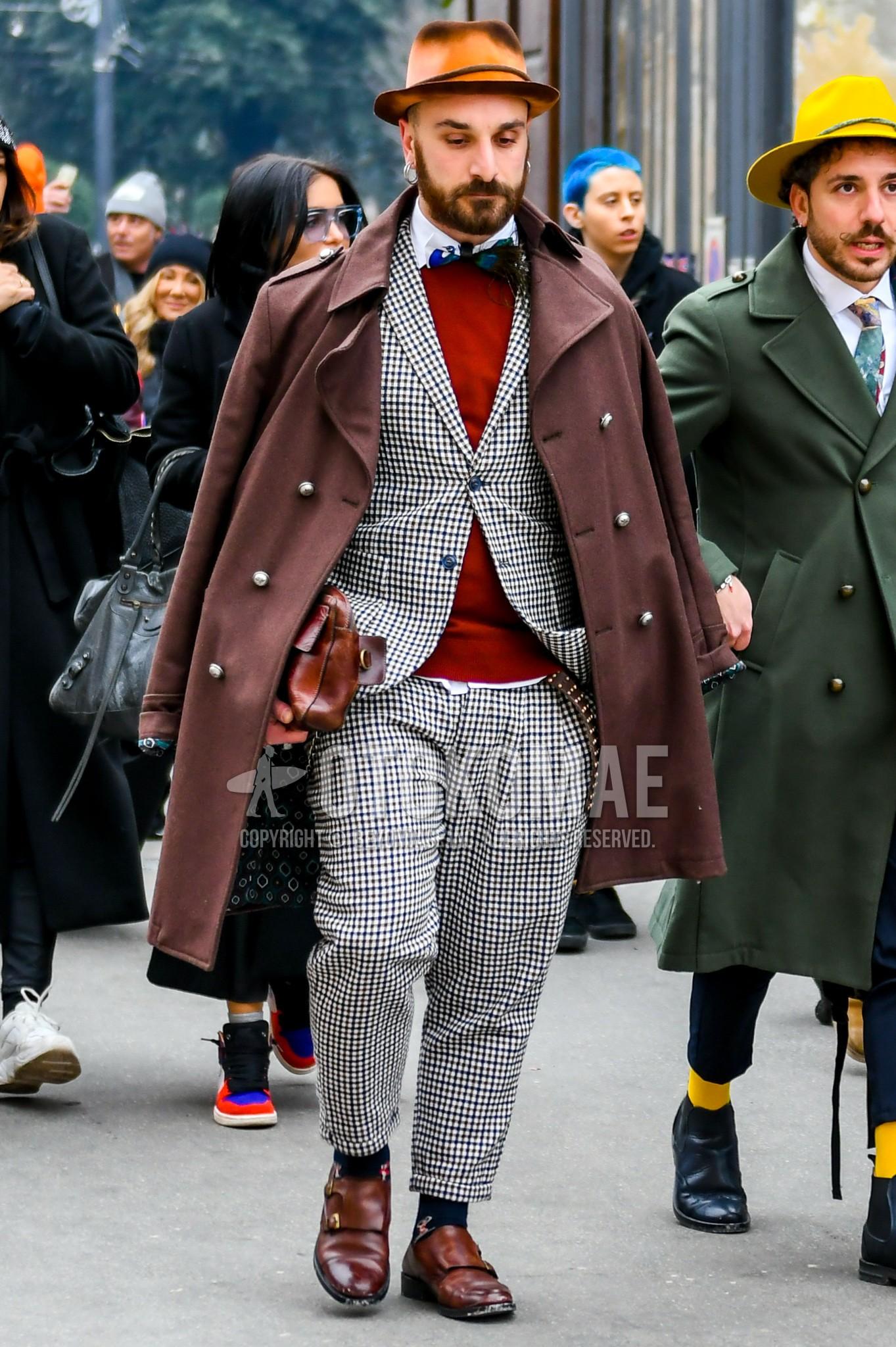 ブラウン無地のハット、ブラウン無地のトレンチコート、ブラウン無地のセーター、白無地のシャツ、ブラウン無地のレザーベルト、黒ソックスのソックス、ブラウンモンクシューズの革靴、ブラウン無地のクラッチバッグ/セカンドバッグ/巾着、グレーチェックのスーツ、マルチカラーネクタイのボウタイを合わせた秋冬のメンズコーデ・着こなし。