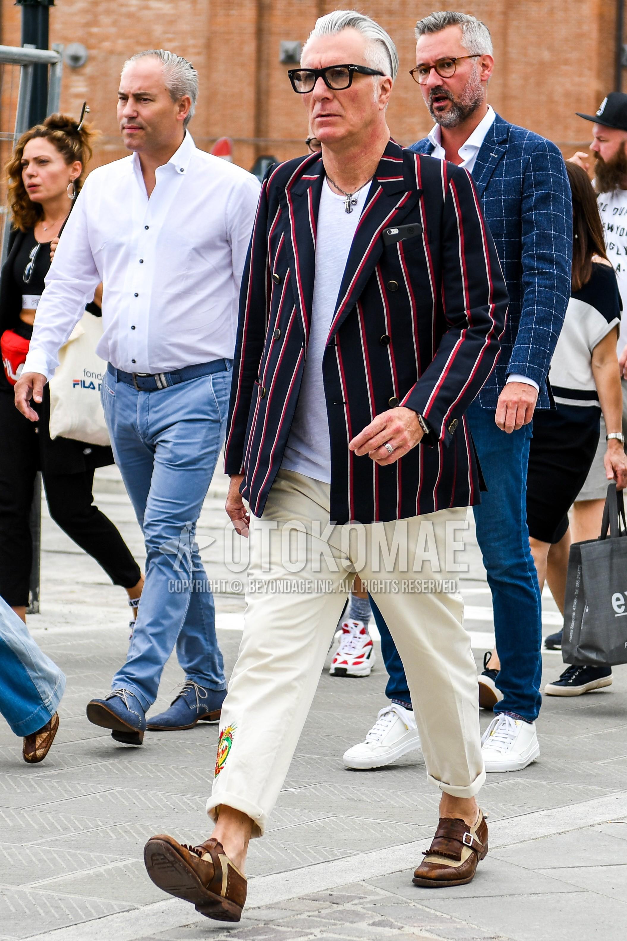 無地のメガネ、ネイビー・レッドストライプのテーラードジャケット、白無地のTシャツ、ベージュ無地のアンクルパンツ、ブラウンモンクシューズの革靴を合わせた春夏秋のメンズコーデ・着こなし。