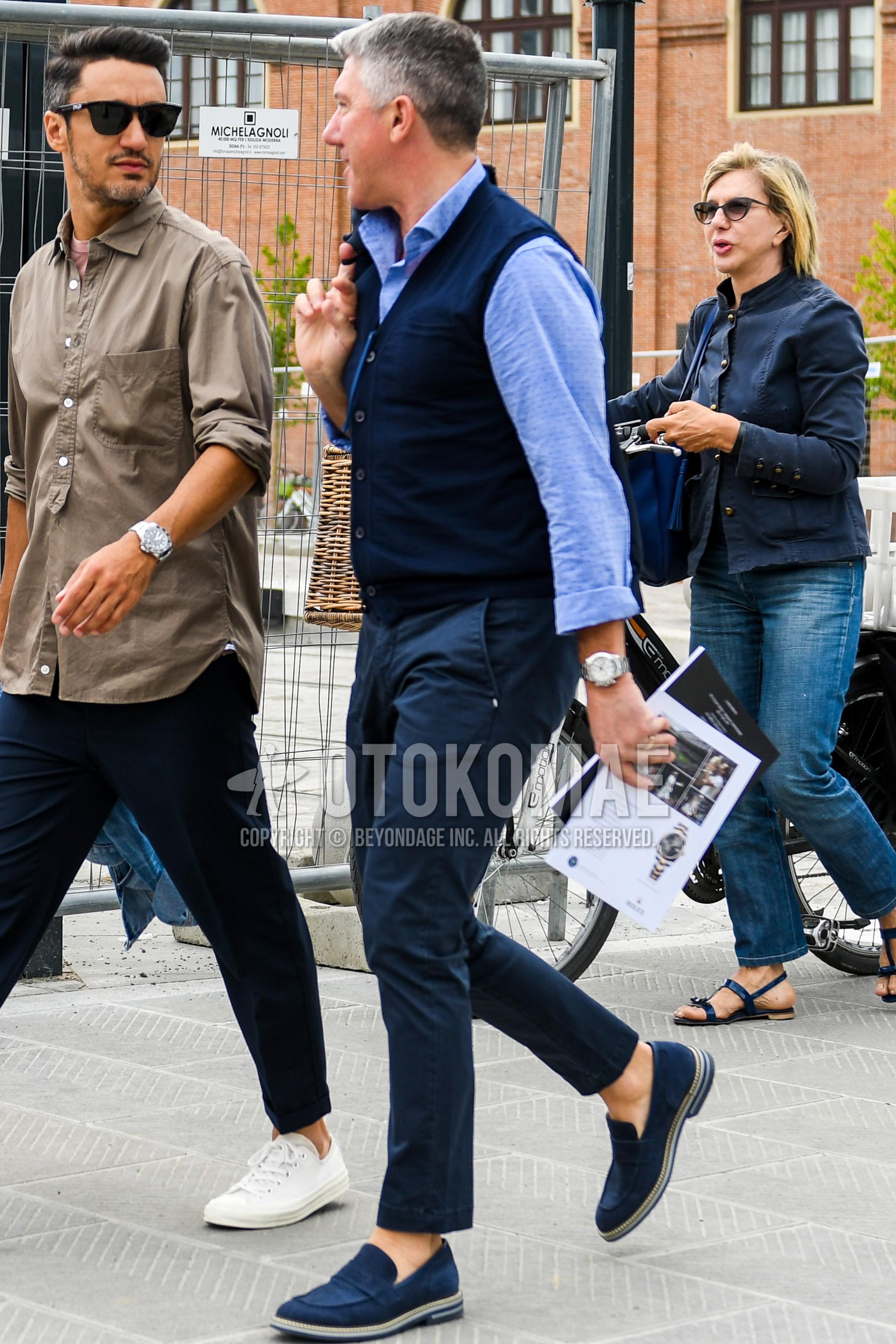 ネイビー無地のジレ、水色無地のシャツ、ネイビー無地のチノパン、ネイビーコインローファーの革靴、スエードシューズの革靴を合わせた春夏秋のメンズコーデ・着こなし。