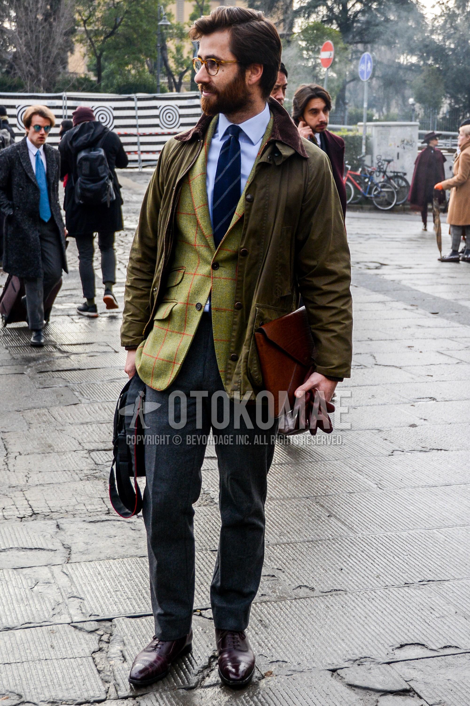 無地のメガネ、オリーブグリーン無地のフィールドジャケット/ハンティングジャケット、グリーンチェックのテーラードジャケット、白無地のシャツ、グレー無地のスラックス、ブラウンストレートチップの革靴、ブラウン無地のクラッチバッグ/セカンドバッグ/巾着、ネイビーレジメンタルのネクタイを合わせた秋冬のメンズコーデ・着こなし。