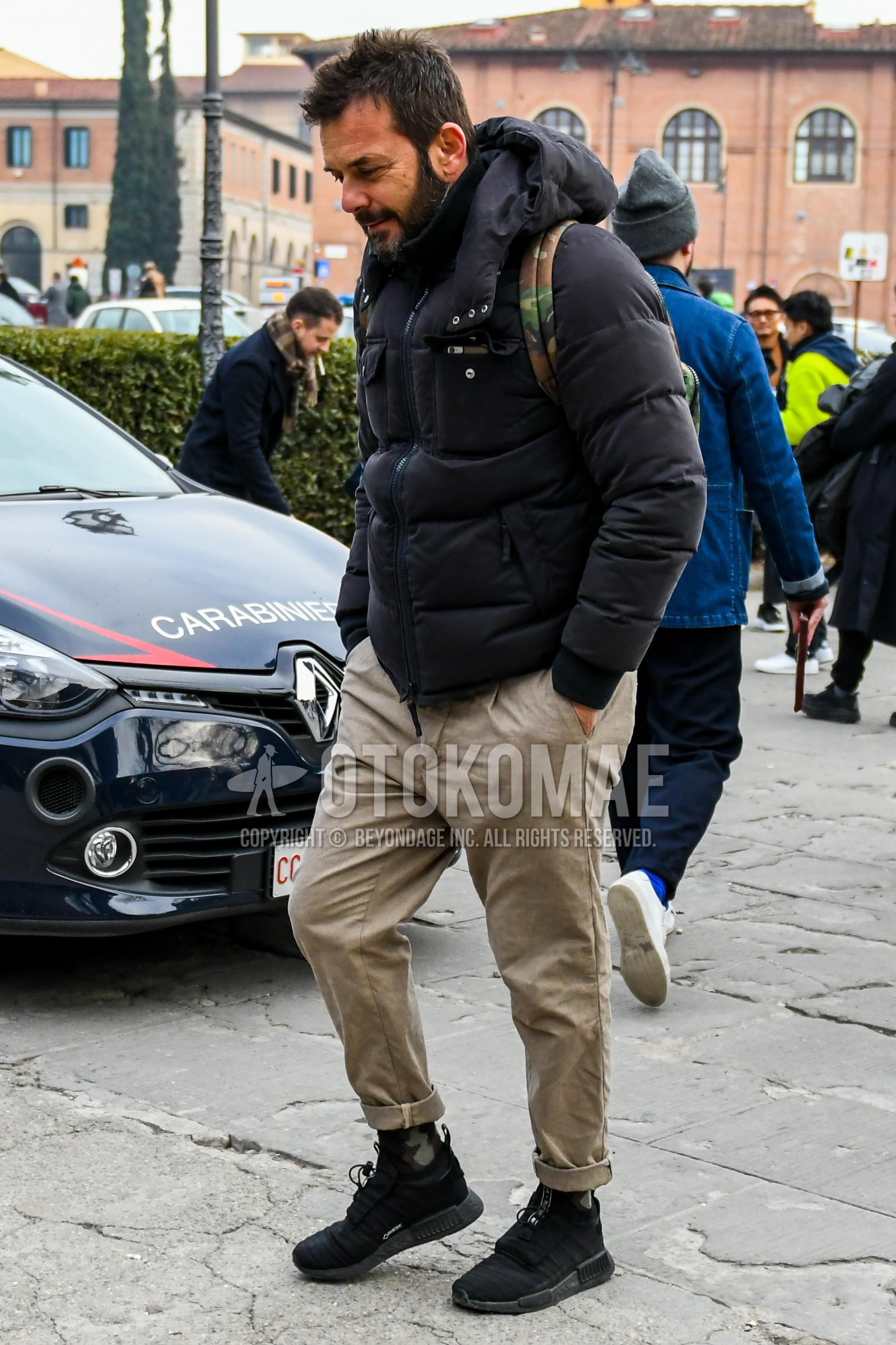 黒無地のダウンジャケット、ベージュ無地のコットンパンツ、マルチカラー迷彩のソックス、黒ローカットのスニーカーを合わせた冬のメンズコーデ・着こなし。