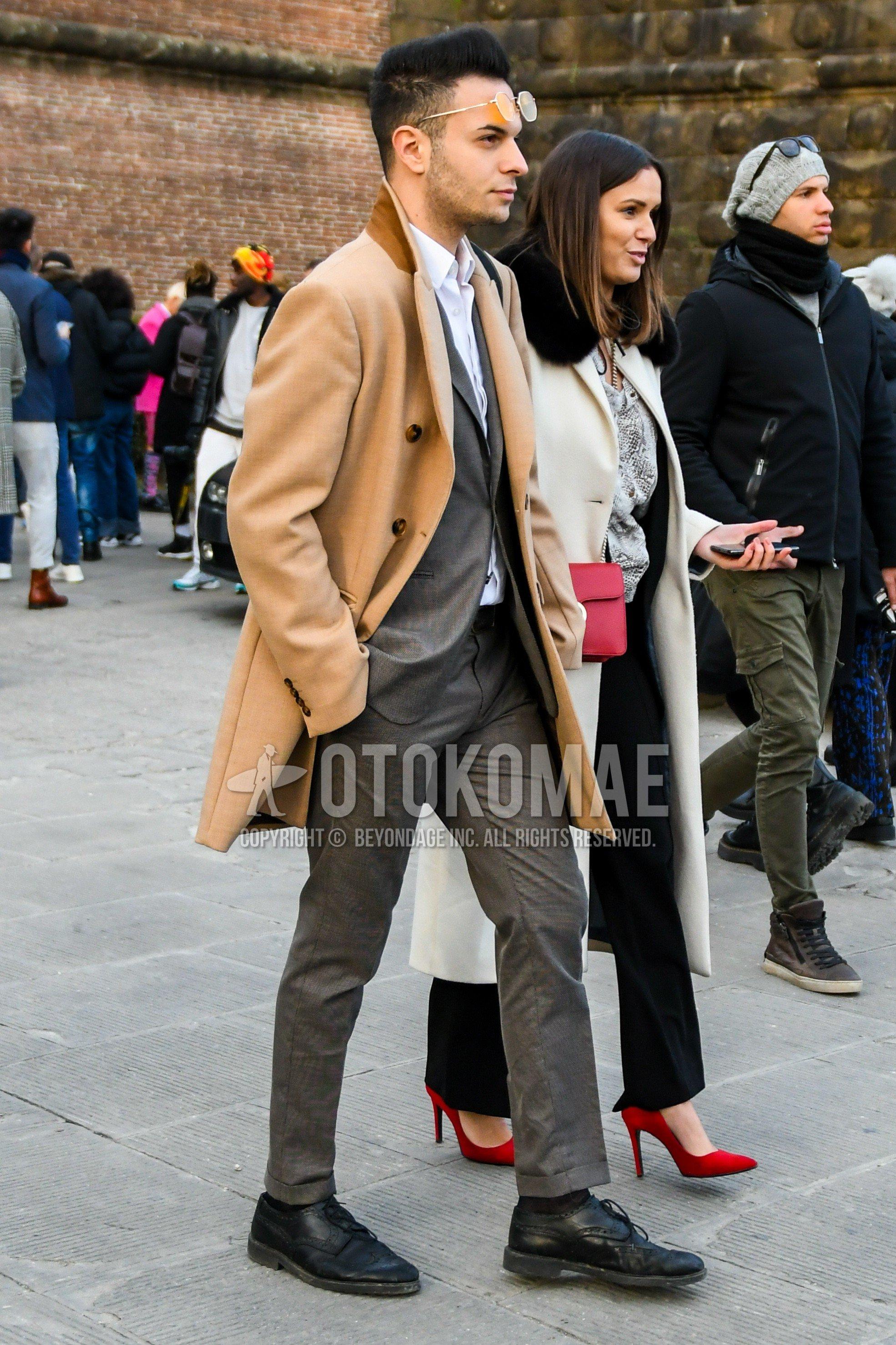 ブラウン無地のチェスターコート、白無地のシャツ、ダークグレー無地のソックス、黒ブローグシューズの革靴、グレー無地のスーツを合わせた冬のメンズコーデ・着こなし。