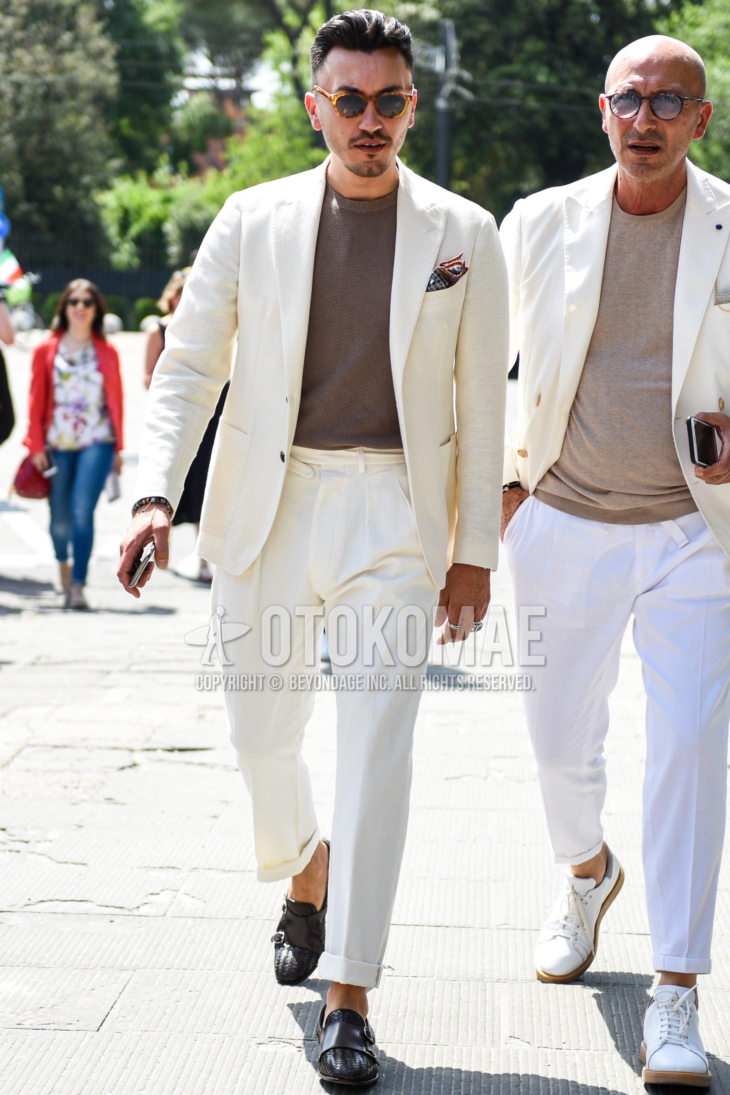 ブラウンべっ甲のサングラス、ニットのブラウン無地のTシャツ、ブラウンモンクシューズの革靴、白無地のスーツを合わせた春夏秋のメンズコーデ・着こなし。