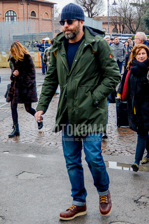 無地のニットキャップ、無地のサングラス、オリーブグリーン無地のフーデッドコート、ネイビー無地のセーター、ブルー無地のデニム/ジーンズ、ブラウンワークのブーツを合わせたメンズコーデ・着こなし。